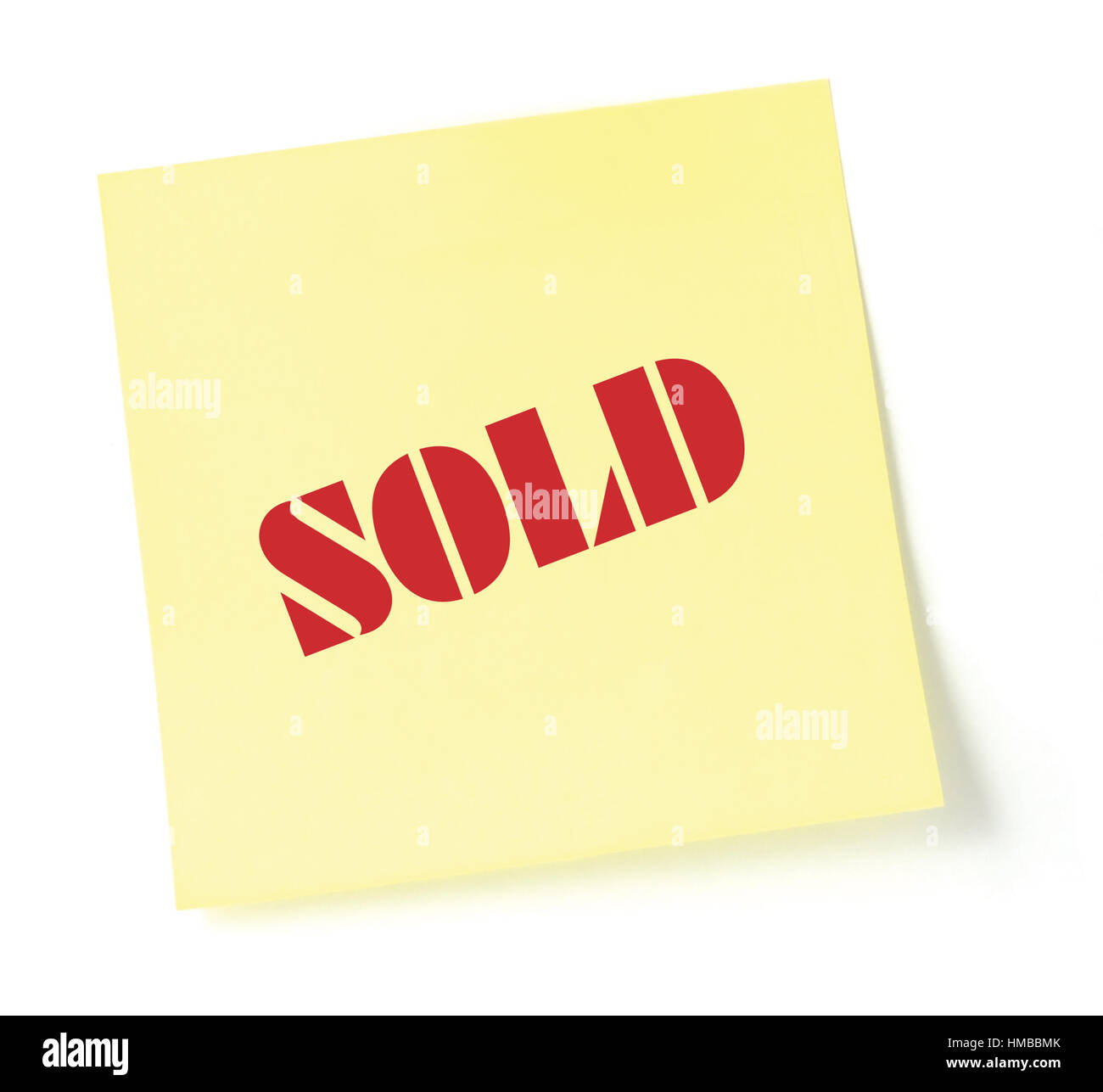 Sticky note indicating item is sold, isolated detailed macro closeup, red text on yellow sticker - Stock Image