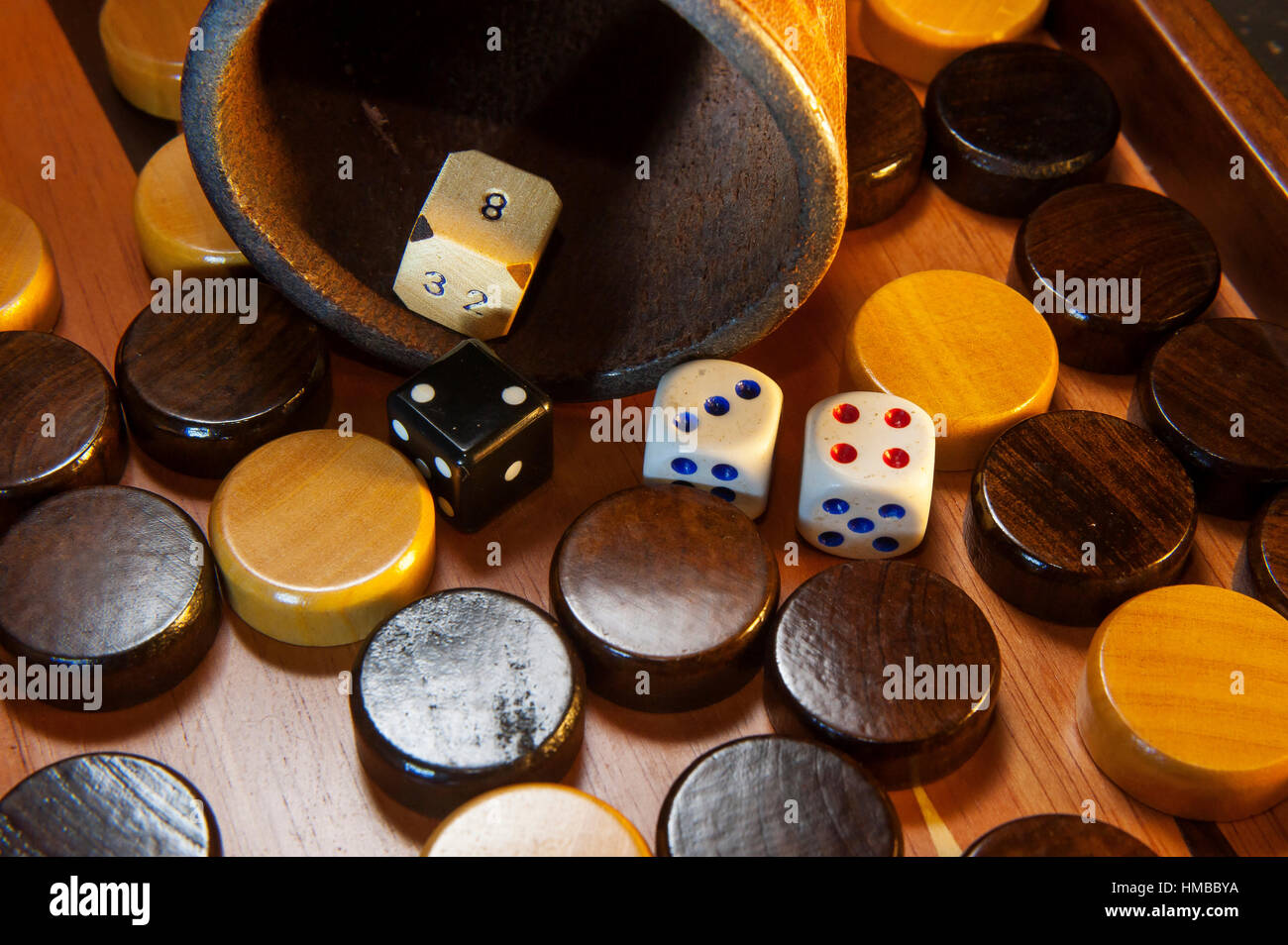 Different type of dice on a gamon board - Stock Image