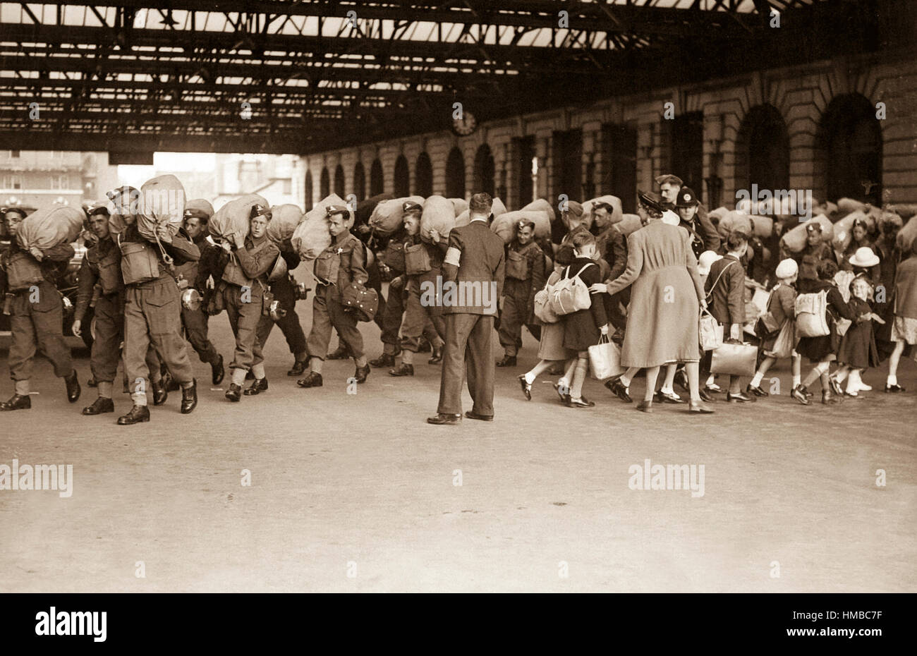 A scene at a London railway station showing troops arriving while children who are being evacuated from London leave - Stock Image