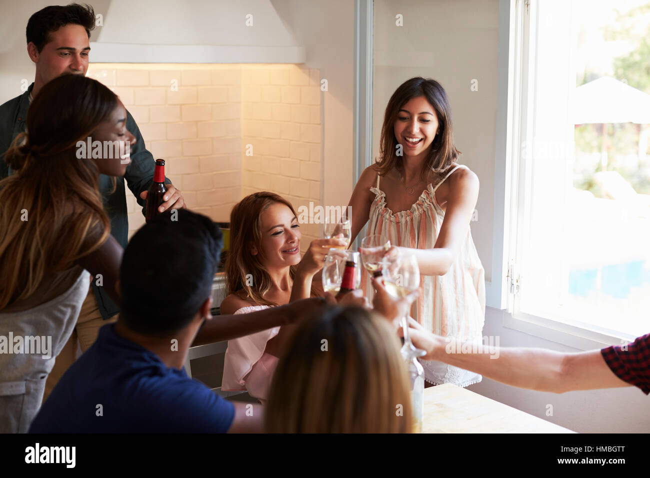 Five friends socialising in the kitchen making a toast - Stock Image