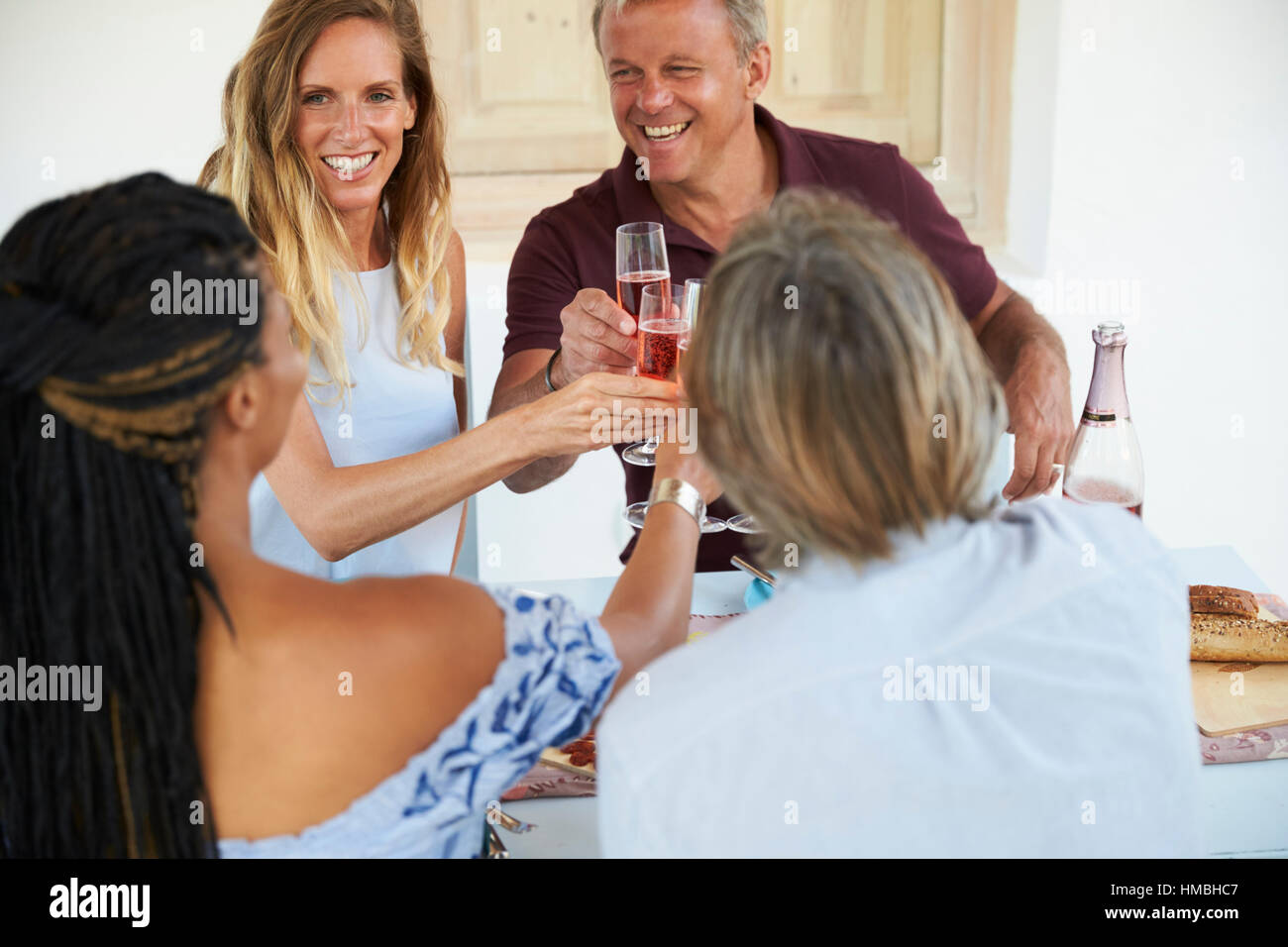 Two couples making a toast before dinner, close up - Stock Image