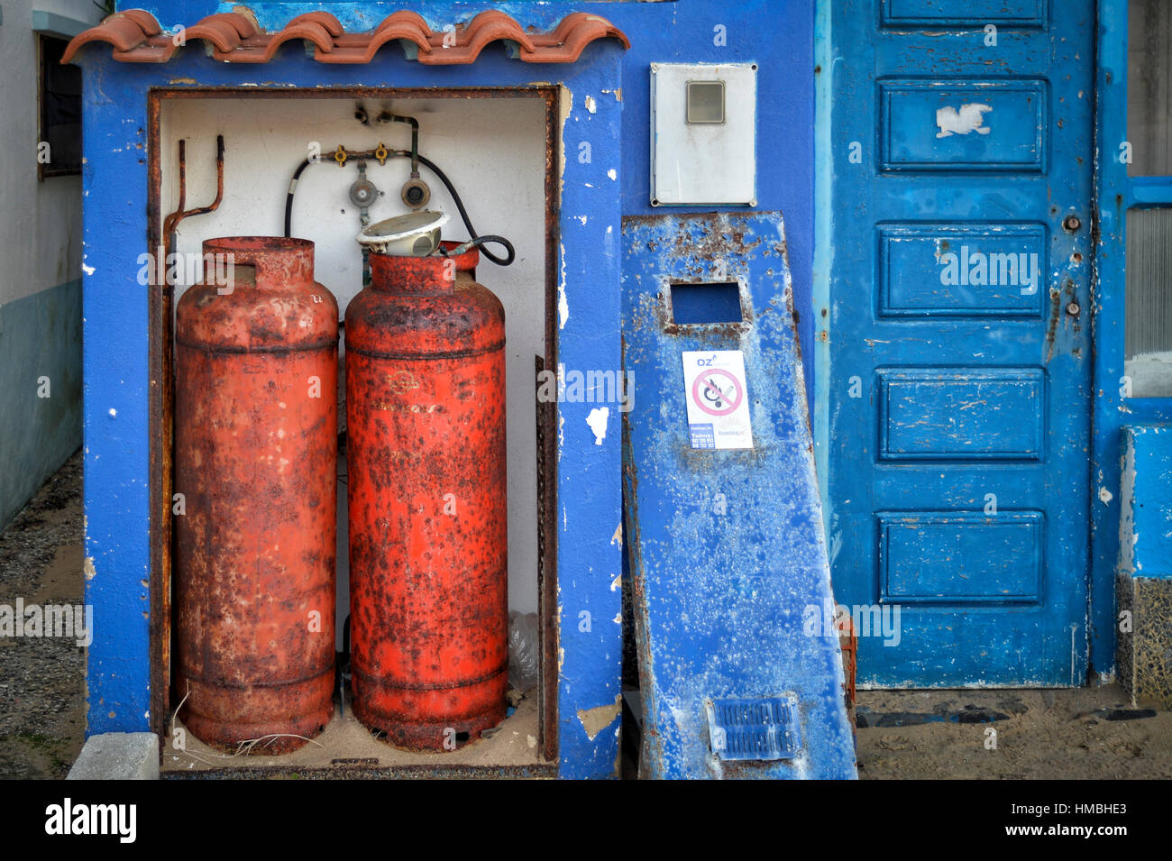 rusty gas fuel canisters outside a building - Stock Image