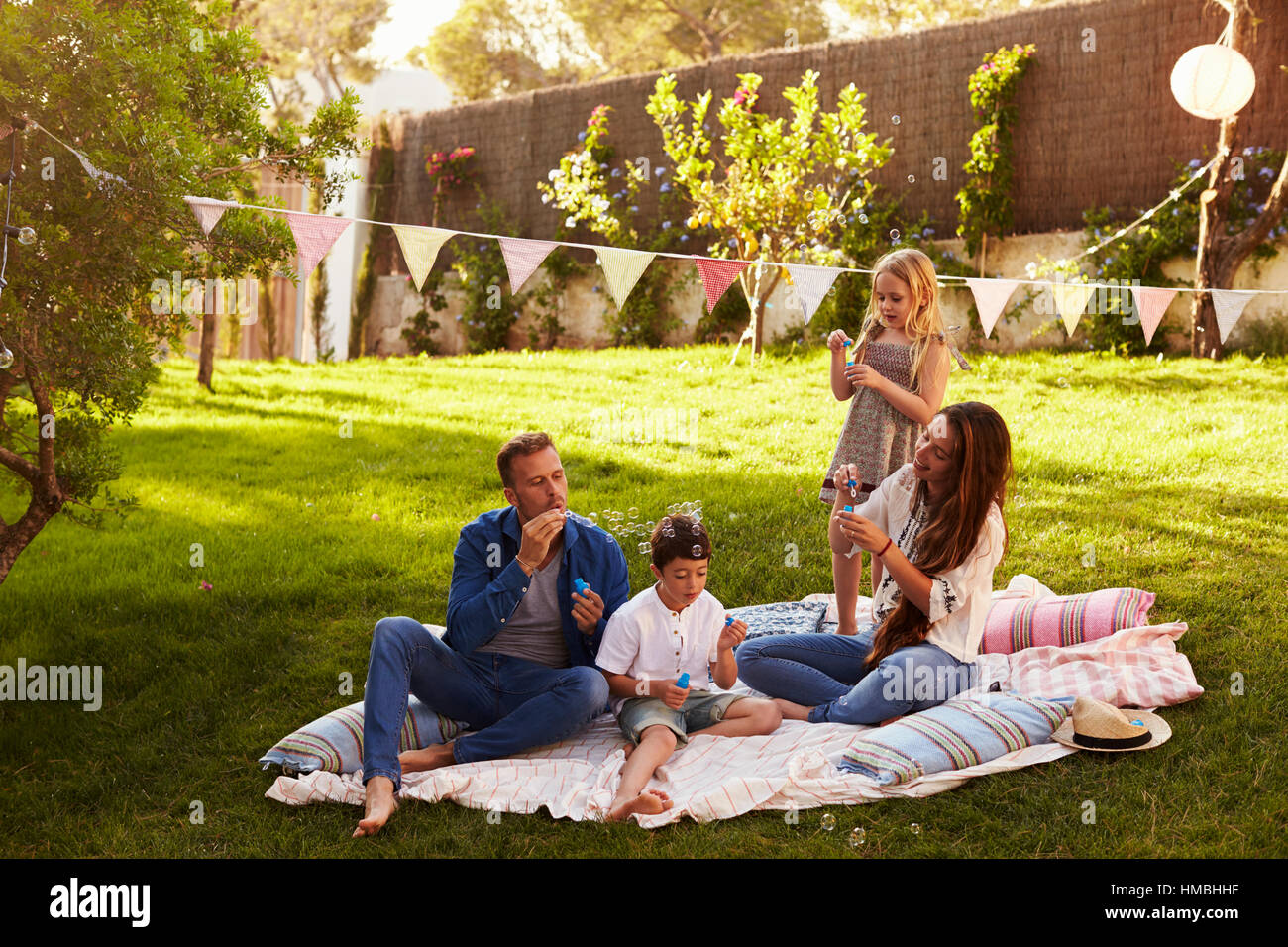 Parents Blowing Bubbles With Children On Blanket In Garden - Stock Image