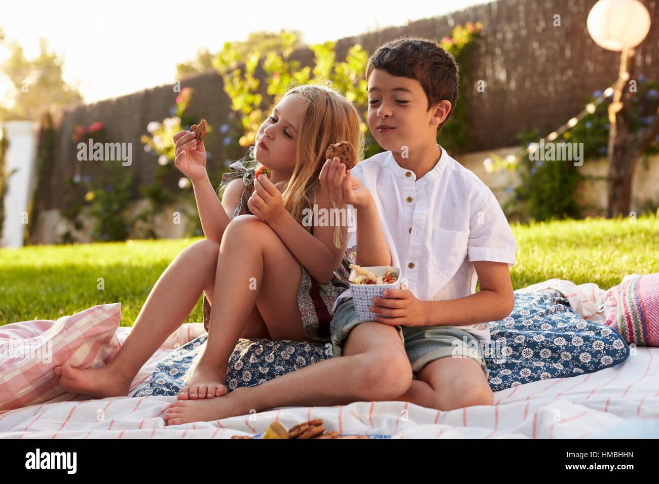 Two Children Enjoying Picnic On Blanket In Garden - Stock Image