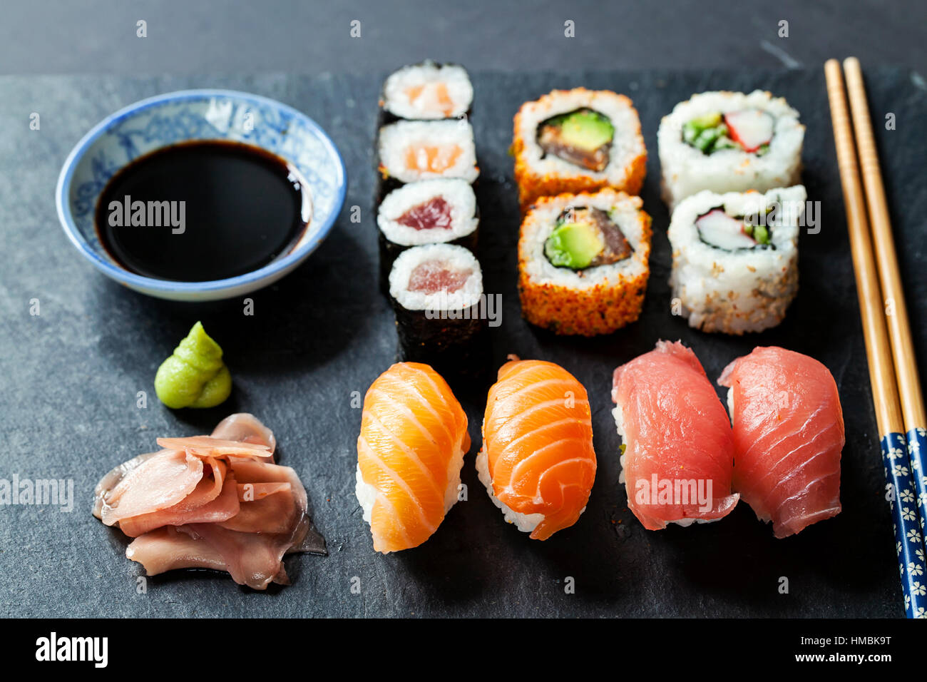 Salmon and tuna sushi on black slate plate - Stock Image
