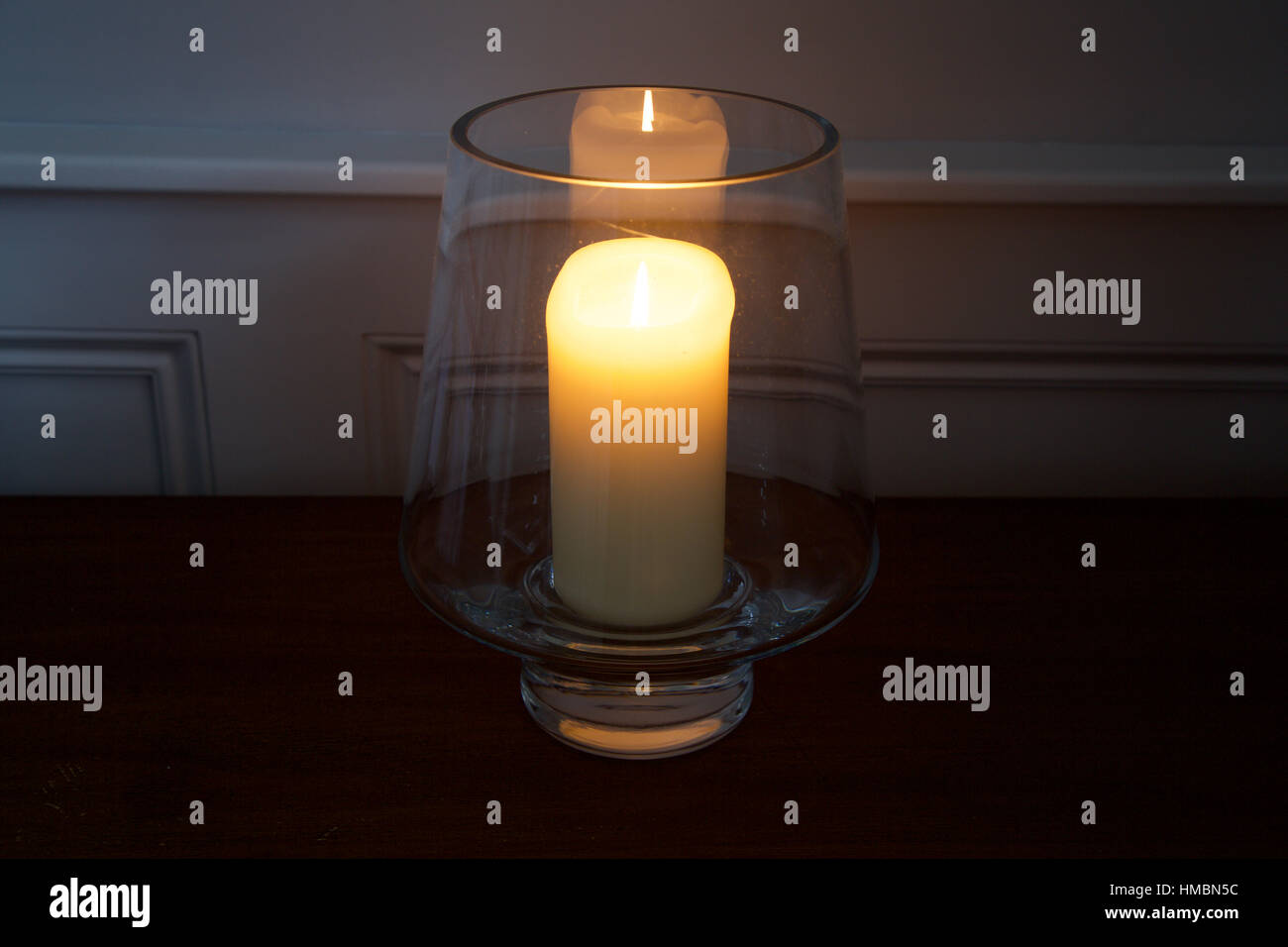 Traditional candle burning in glass holder on table in hallway with glowing flame cosy and creating Danish hygge - Stock Image