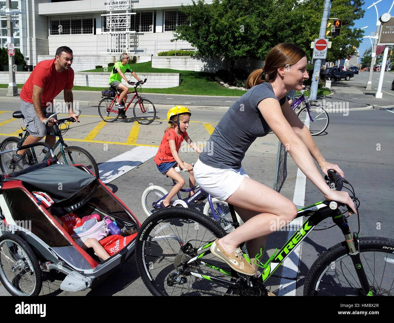 A woman on a bicycle pulls a baby in an attachment while other people bike through downtown streets during he second - Stock Image