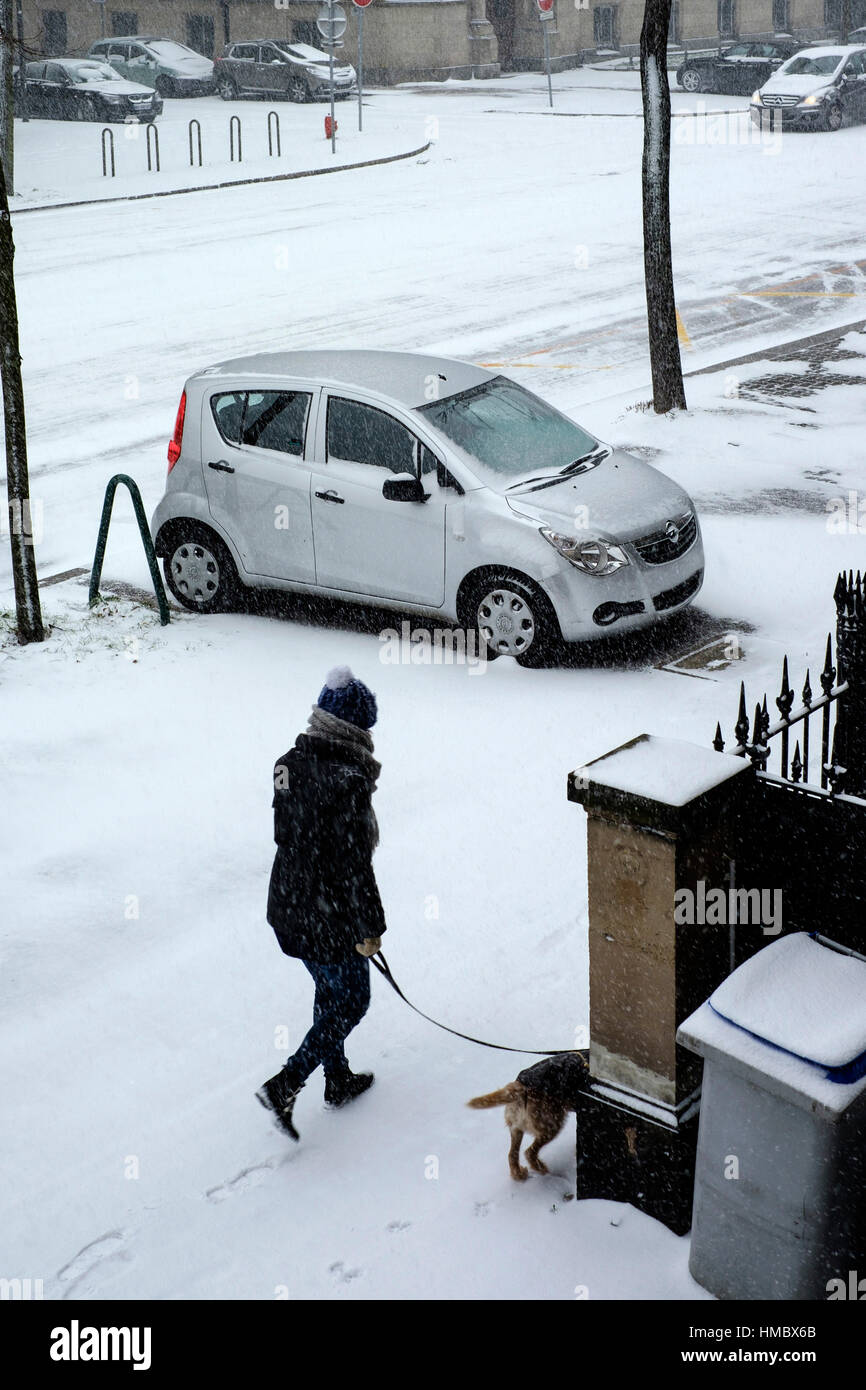Parked car on pavement, woman walking her dog, snow in town, Strasbourg, Alsace, France. - Stock Image