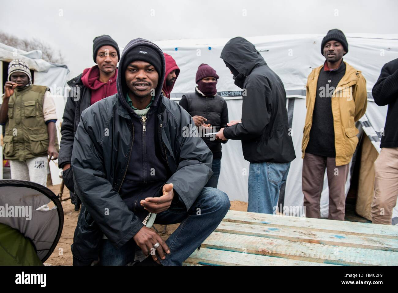 Calais, France. Group of Sudani migrants in The Jungle of Calais, deliberating about ways to travel to the UK. - Stock Image