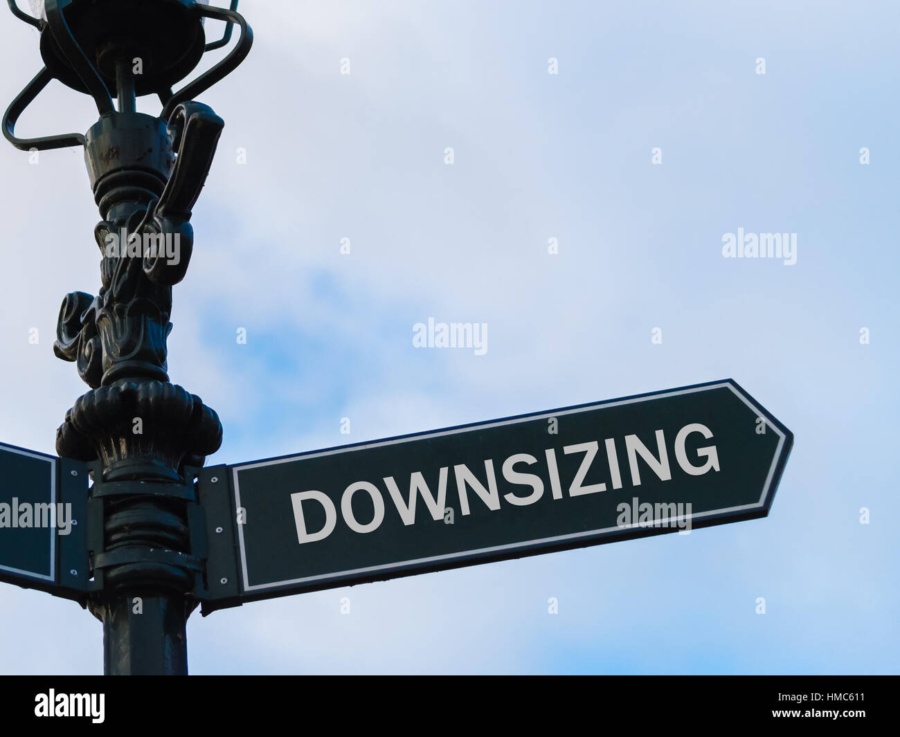 Street lighting pole with conceptual message Downsizing on directional arrow over blue cloudy background. - Stock Image
