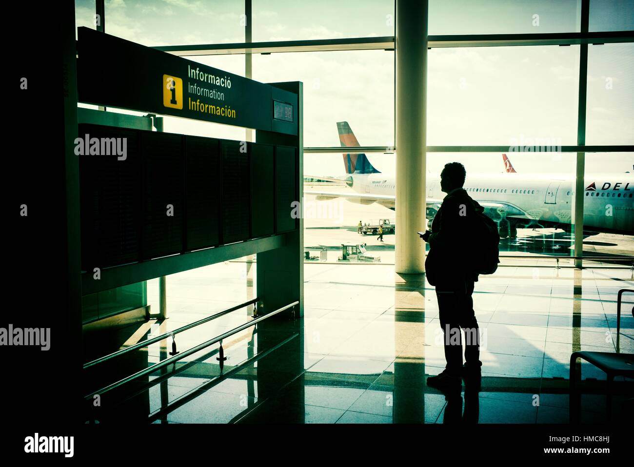 Passenger in Barcelona airport, looking the airplanes through the window, toward the runway, by the information Stock Photo