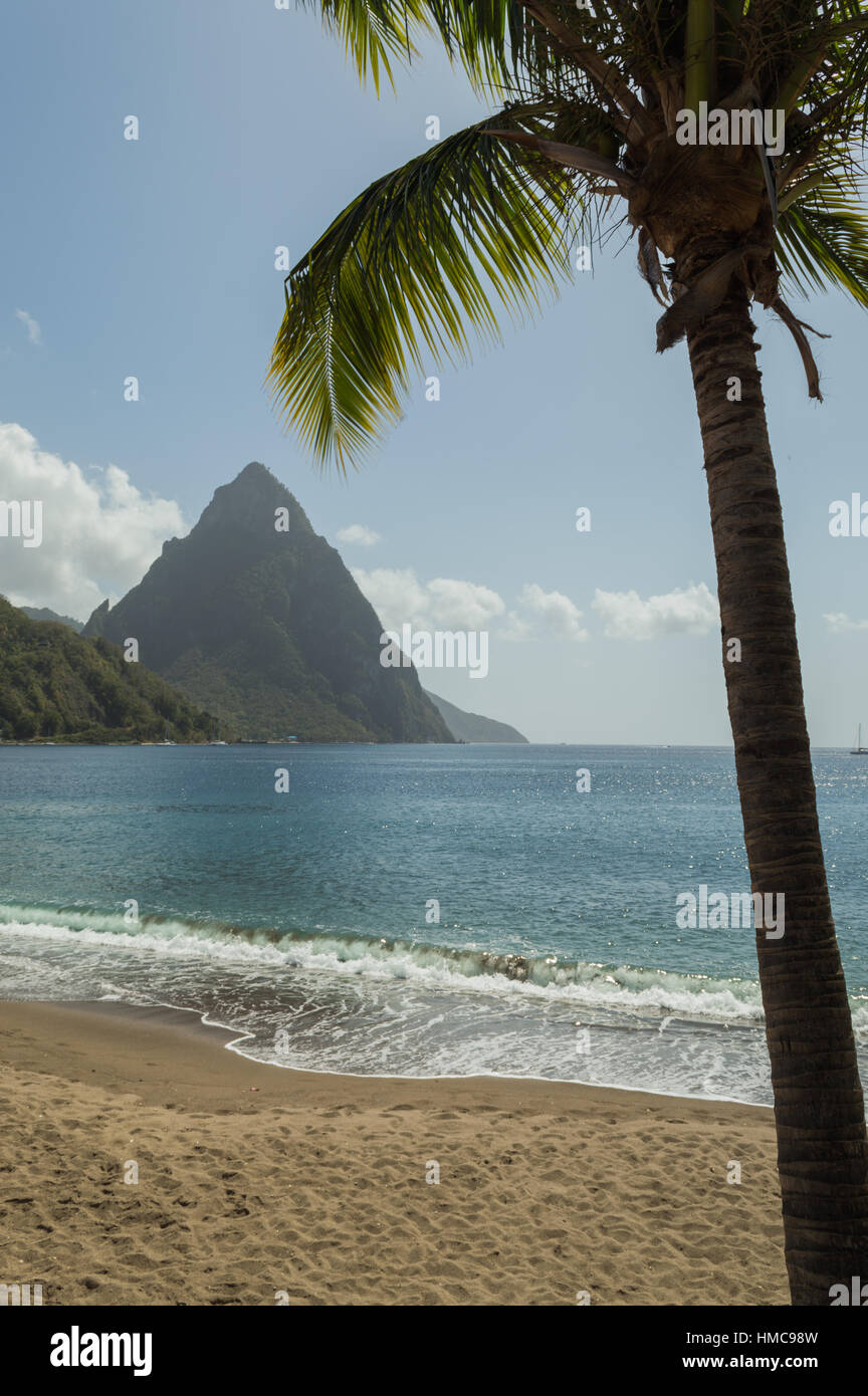 Beach view across the bay at Soufriere to the sea and Piton mountain. Framed with a palm tree Stock Photo