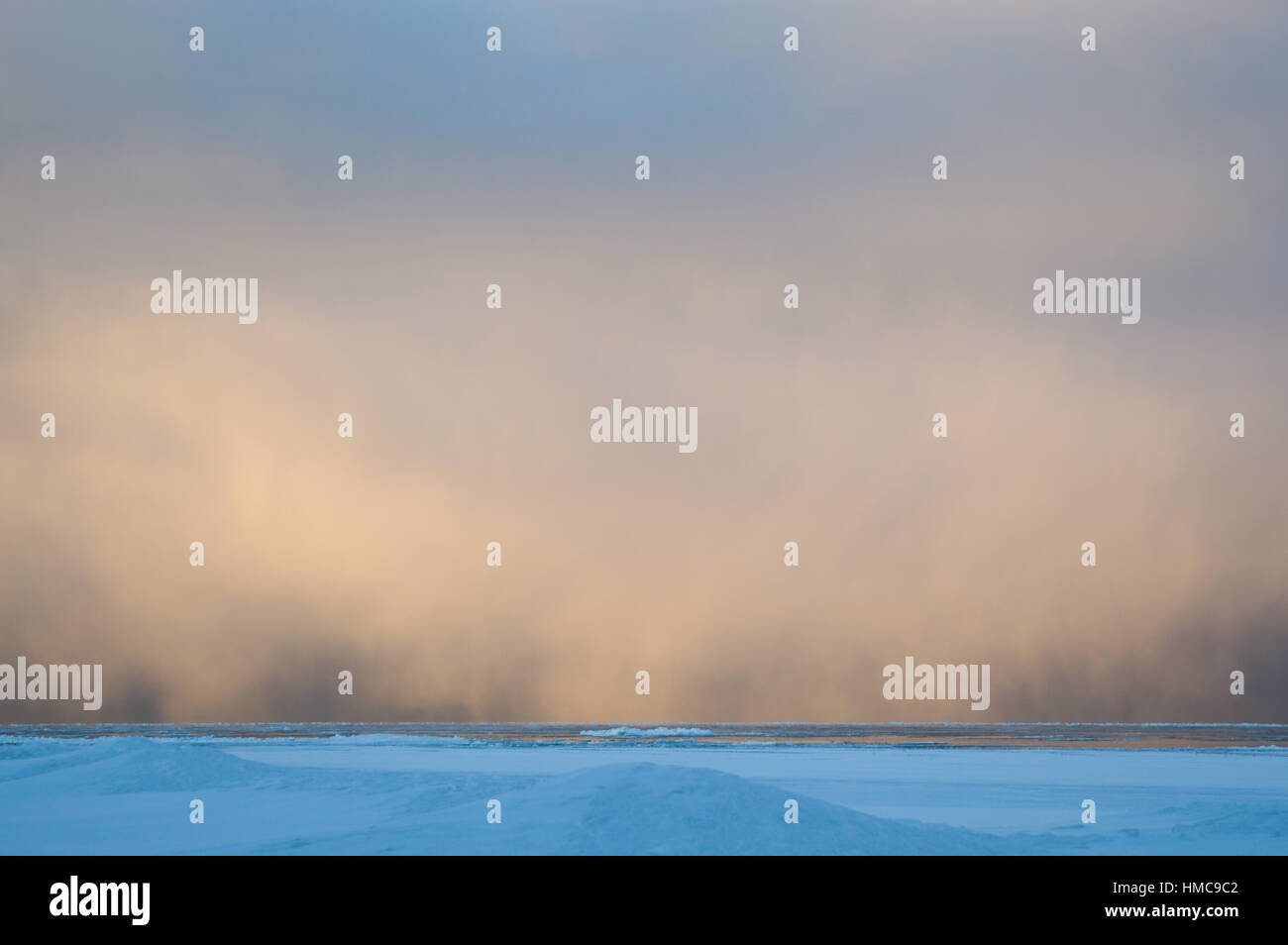 Sidelit snow squall clouds rolling in across the frozen Lake Huron at sunrise.  Ice floats on the still calm water. - Stock Image