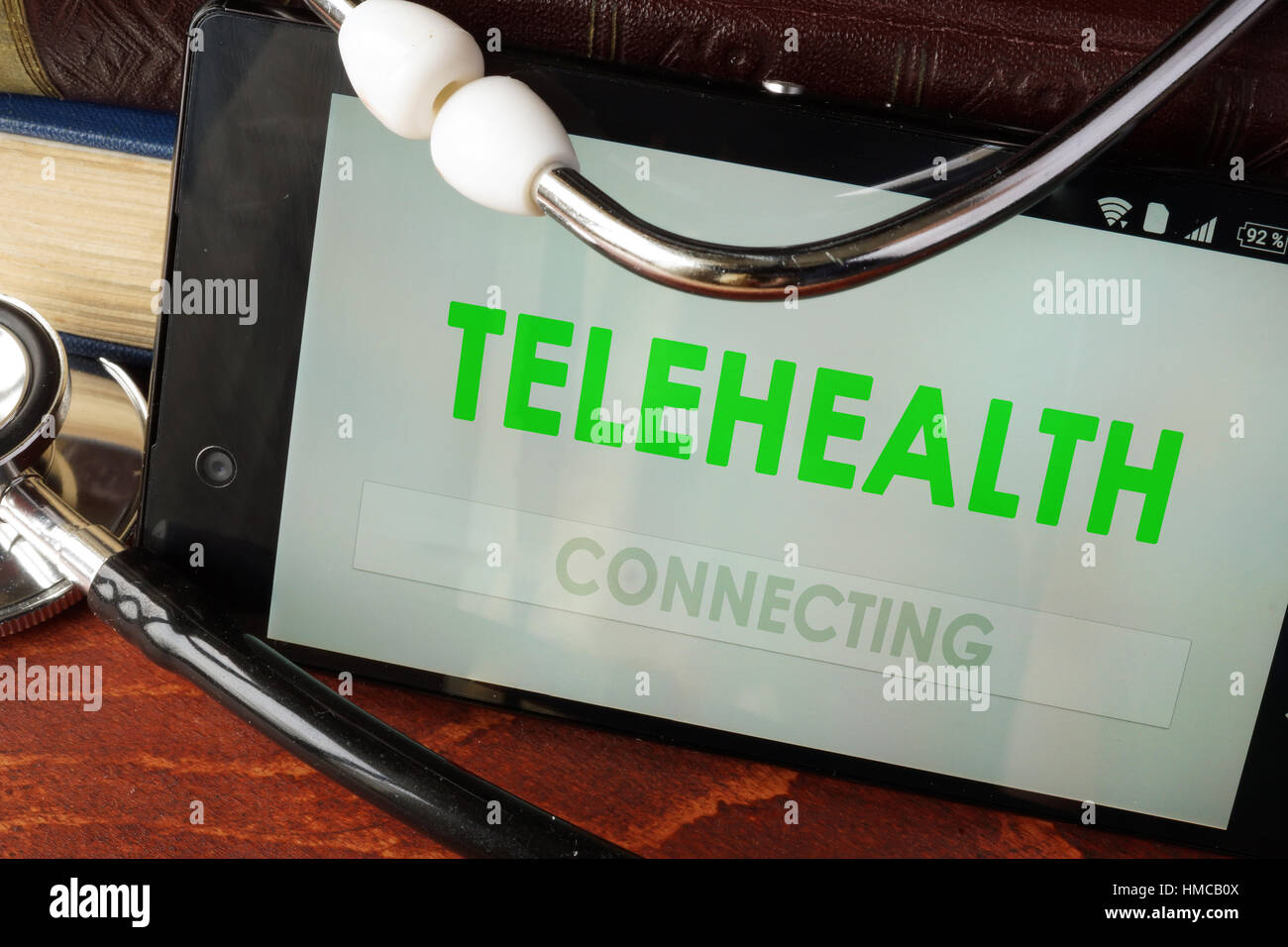Telehealth apps open in a smartphone and stethoscope. - Stock Image