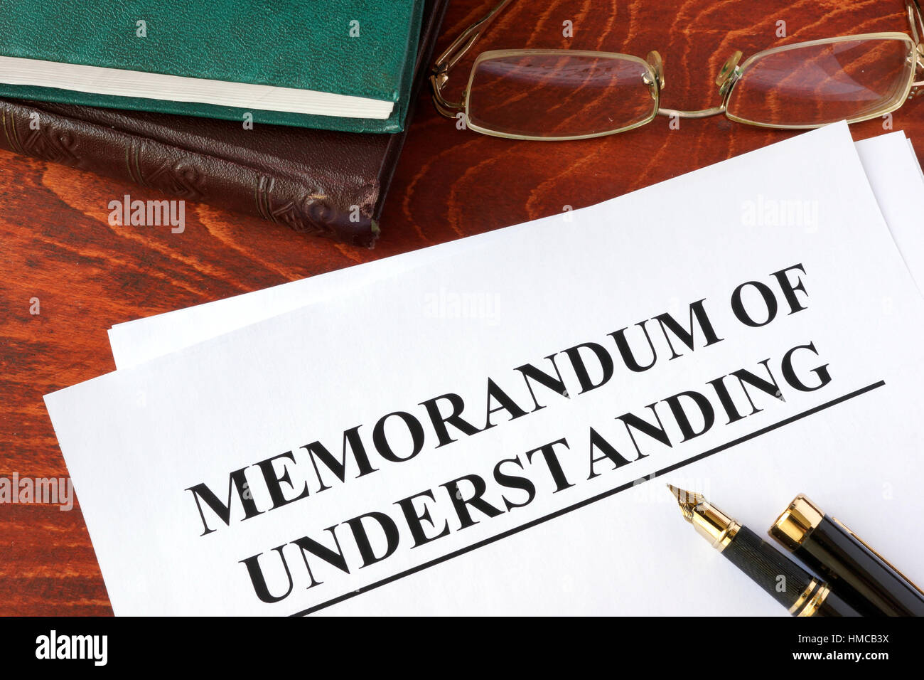 Memorandum of understanding MOU on a table and a pen. - Stock Image