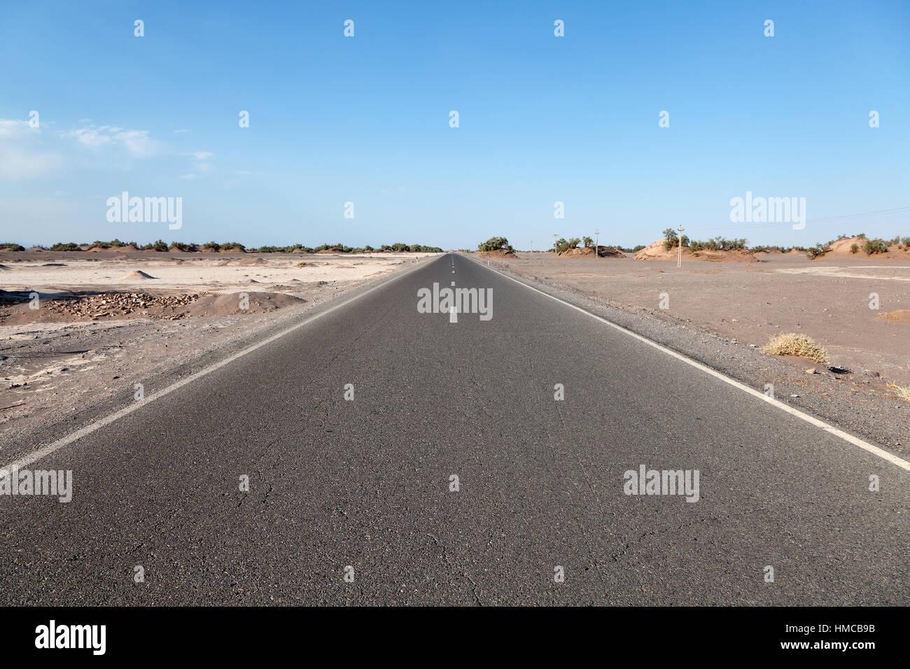 Empty road through Dasht-e Loot desert, Iran - Stock Image