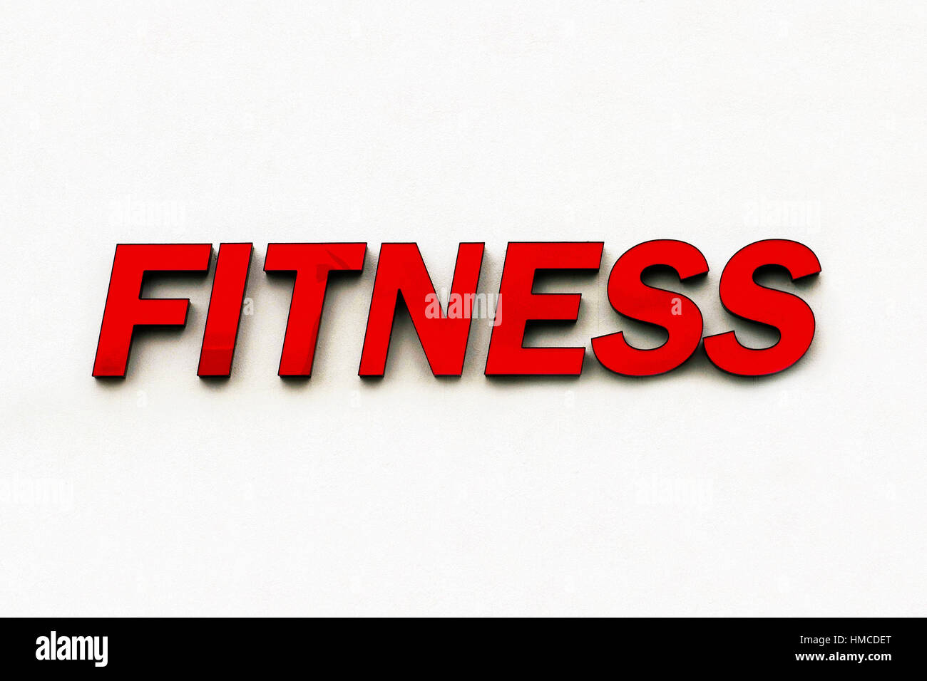 Red plastic sign of the word 'Fitness' advertises a gymnasium and is isolated on a white wall background. - Stock Image