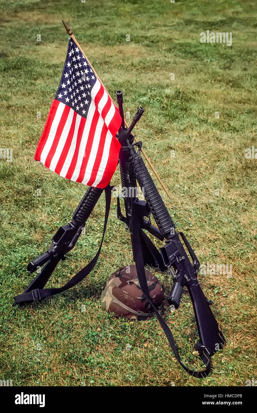Patriotic symbolism memorial to fallen military made of a small American flag propped on a tripod of three M-16 - Stock Image