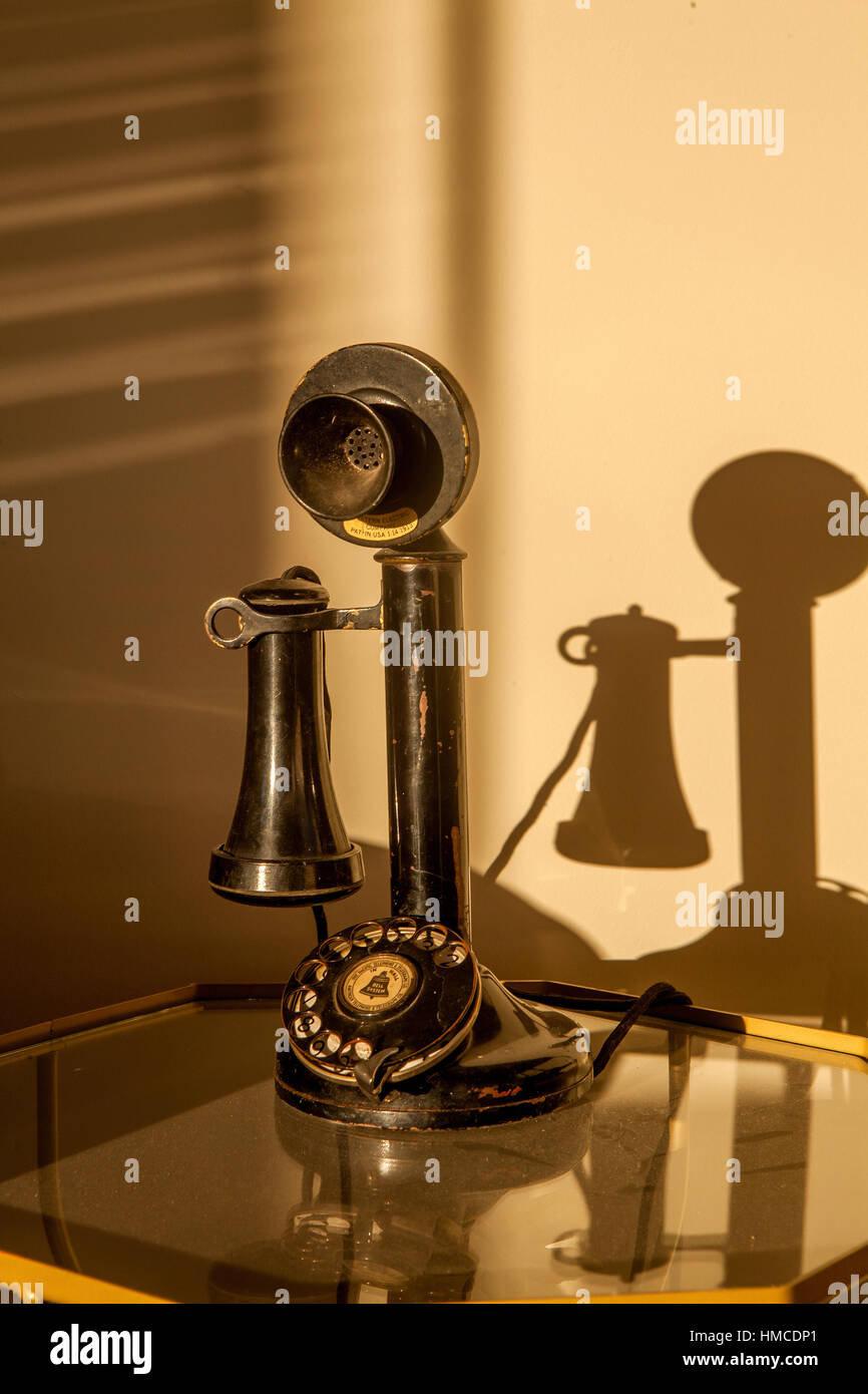 An old fashioned black candlestick telephone with rotary dial sits on a glass table with strong shadows on the wall. - Stock Image