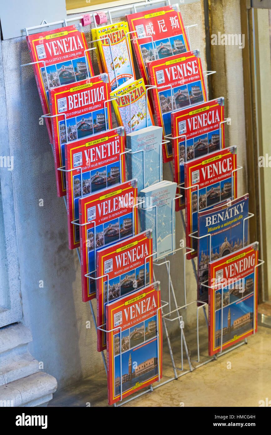 Travel Guide Books in different languages for sale on display in rack at Venice, Italy in January - Stock Image