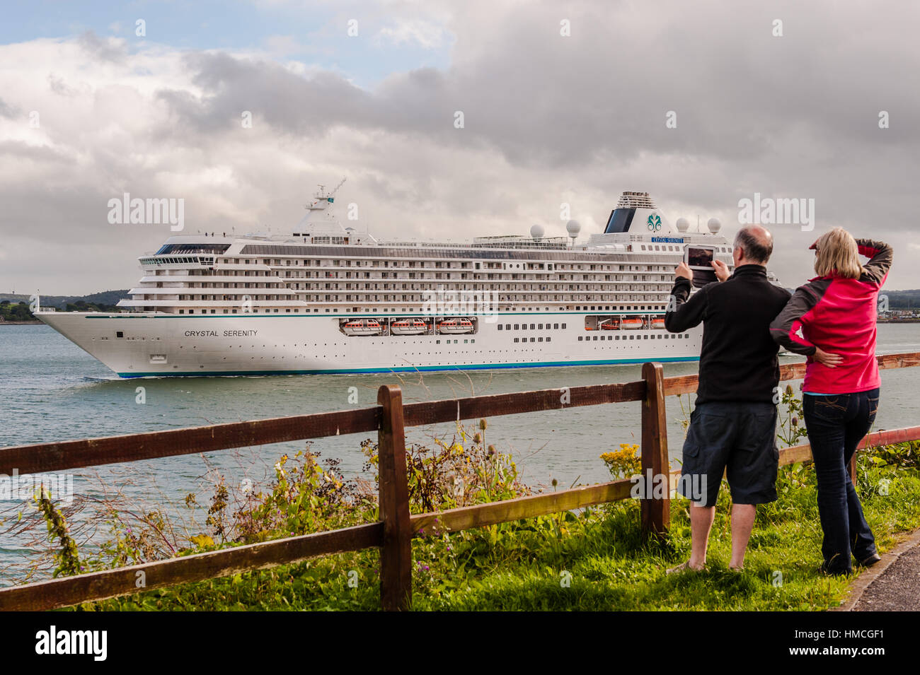Man and woman watch and film the cruise ship Crystal Serenity depart from Cobh, Ireland with copy space. - Stock Image