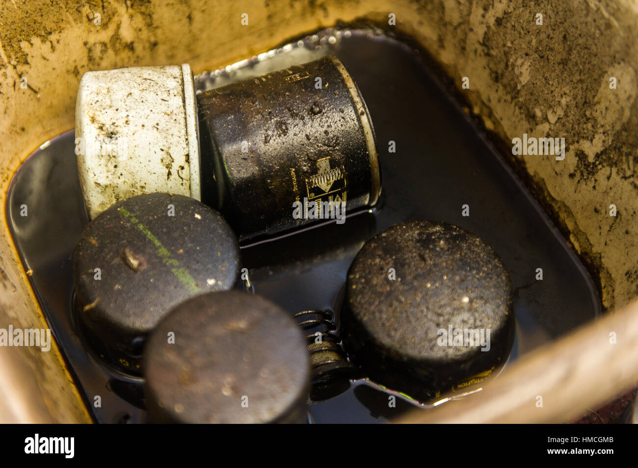 Old and used car oil filters in a bowl full of dirty/used oil. - Stock Image