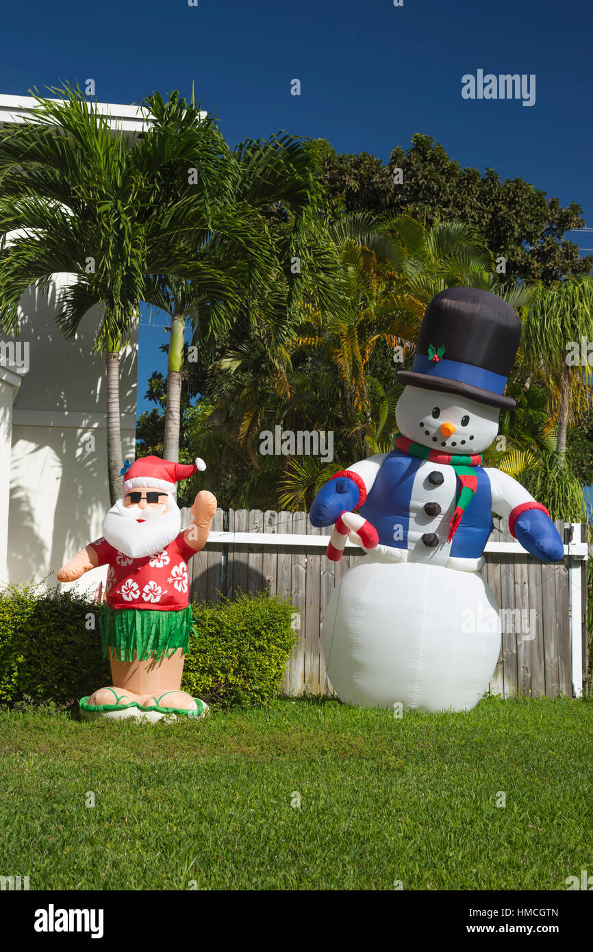 INFLATABLE SANTA CLAUS AND SNOWMAN IN FRONT OF PALM TREES IN RESIDENTIAL FRONT YARD MIAMI FLORIDA USA - Stock Image