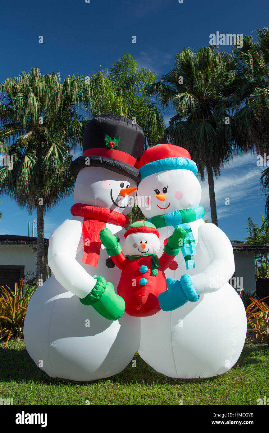 giant inflatable snowman and family in front of palm trees in stock