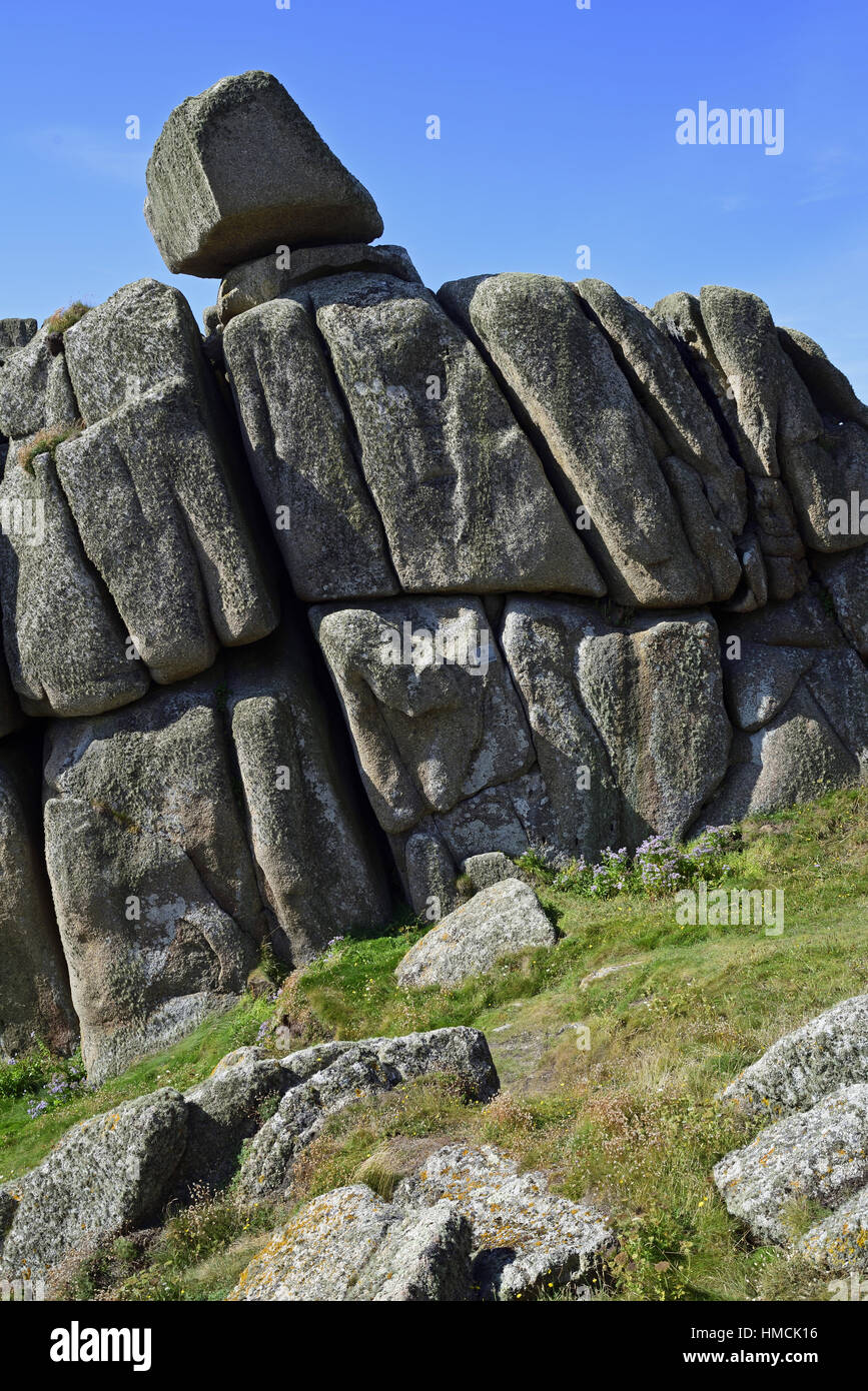 Logan Rock, Treen, Cornwall, precariously balanced on massive blocks of granite. A sign on the rock face below points - Stock Image