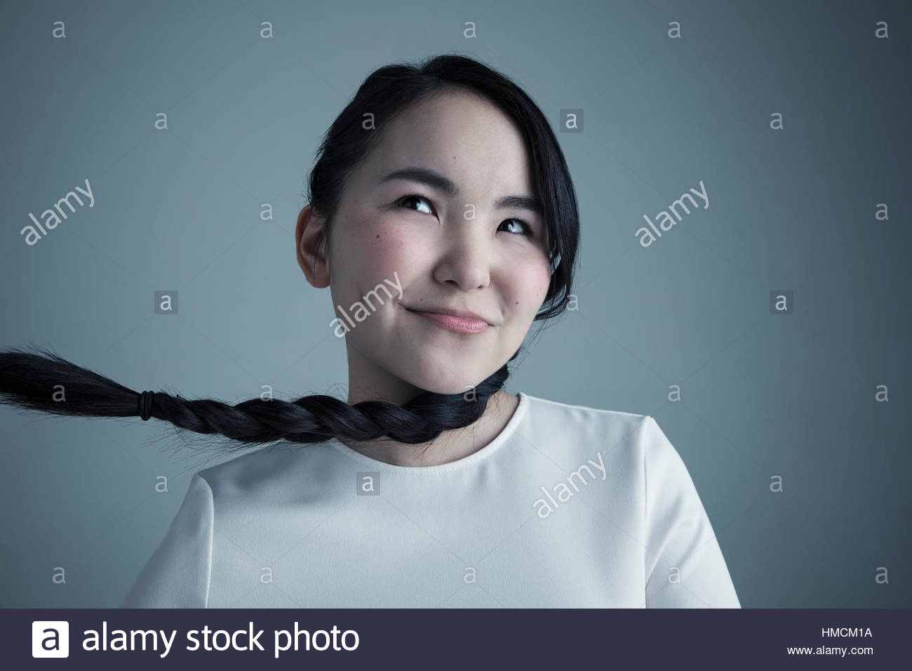 Portrait mischievous Asian young woman with long black braided hair - Stock Image