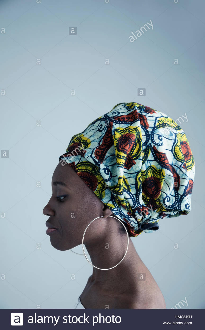 Profile portrait serious African American woman wearing gele headscarf and large hoop earrings - Stock Image
