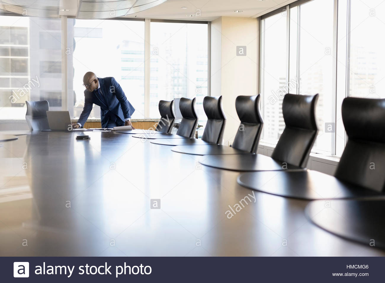 Male lawyer working at laptop in conference room - Stock Image