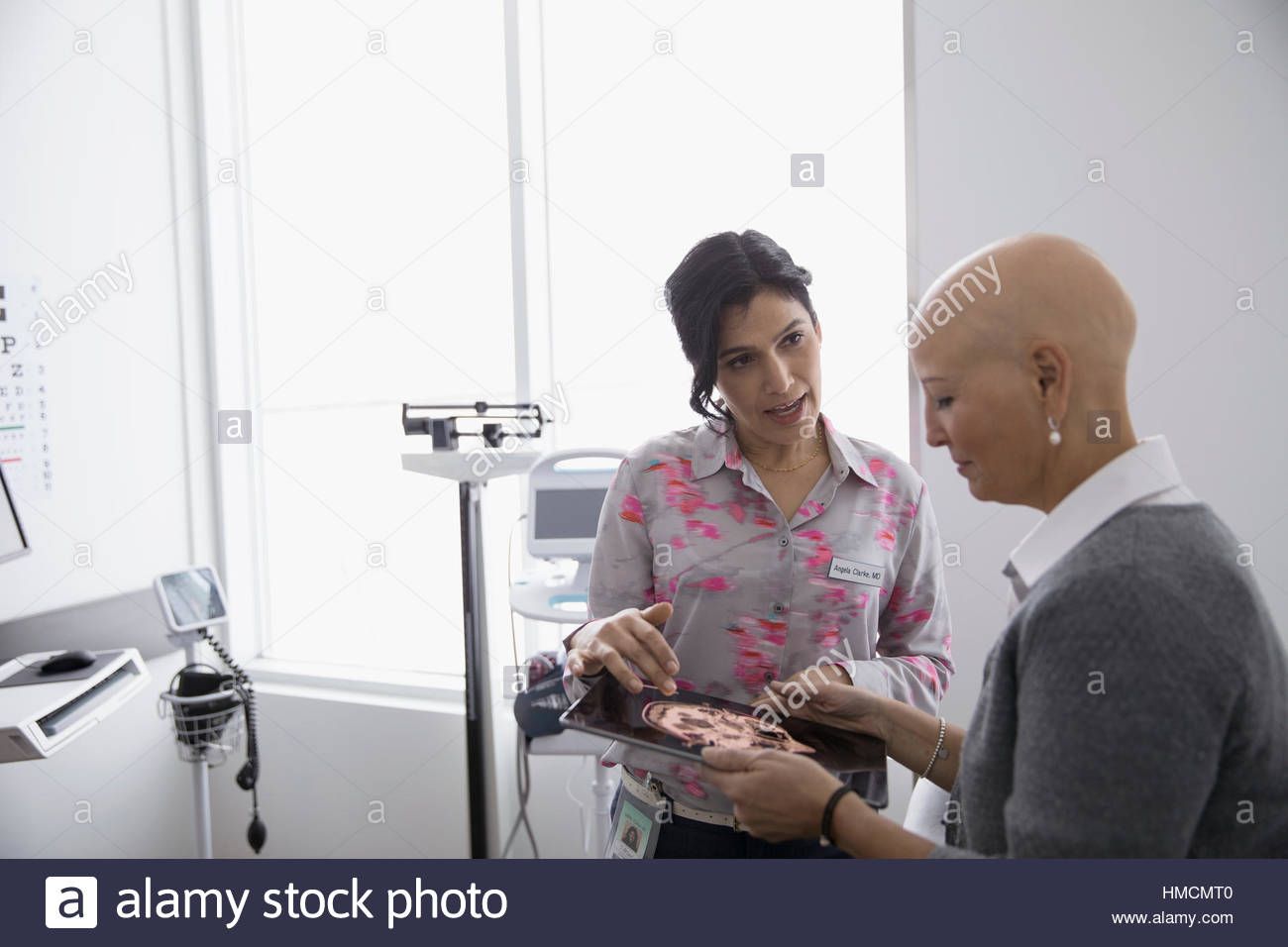 Female doctor showing digital brain scan on digital tablet to bald cancer patient in clinic examination room - Stock Image