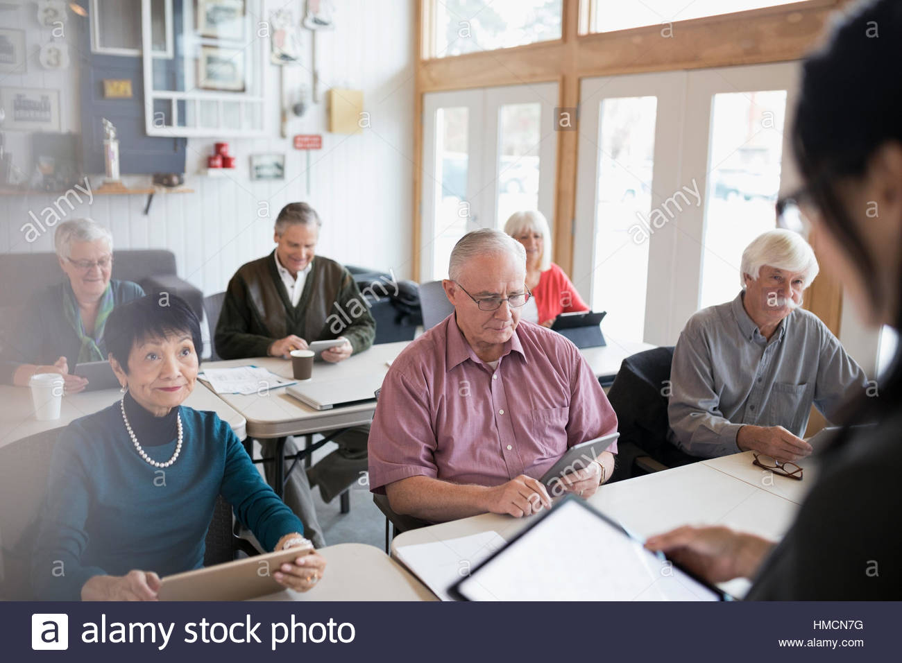 Teacher and senior adults using digital tablets in classroom - Stock Image