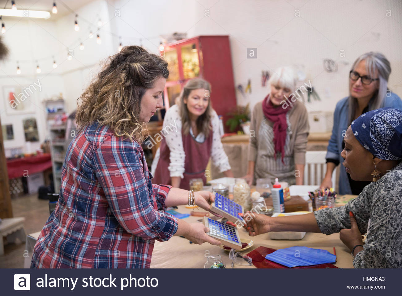 Instructor teaching women in mosaic art and craft class - Stock Image