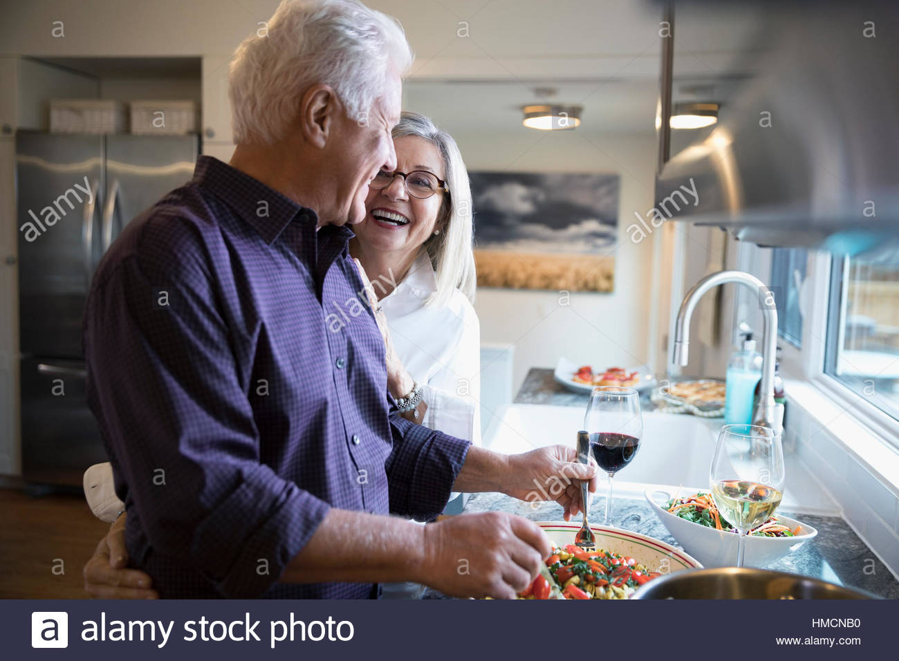Affectionate senior couple laughing cooking and drinking wine in kitchen - Stock Image