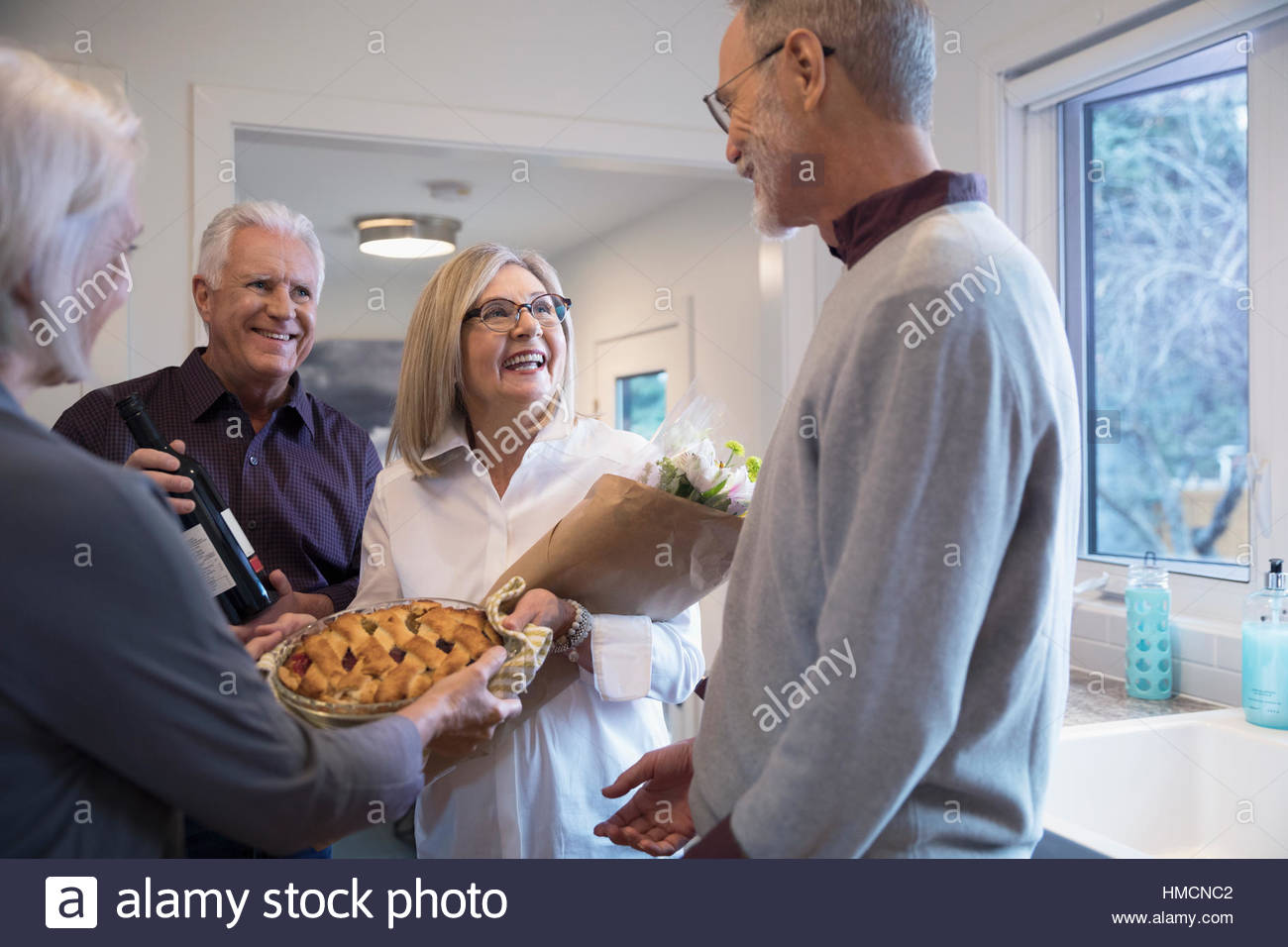 Senior couple with flowers and pie arriving at dinner party - Stock Image