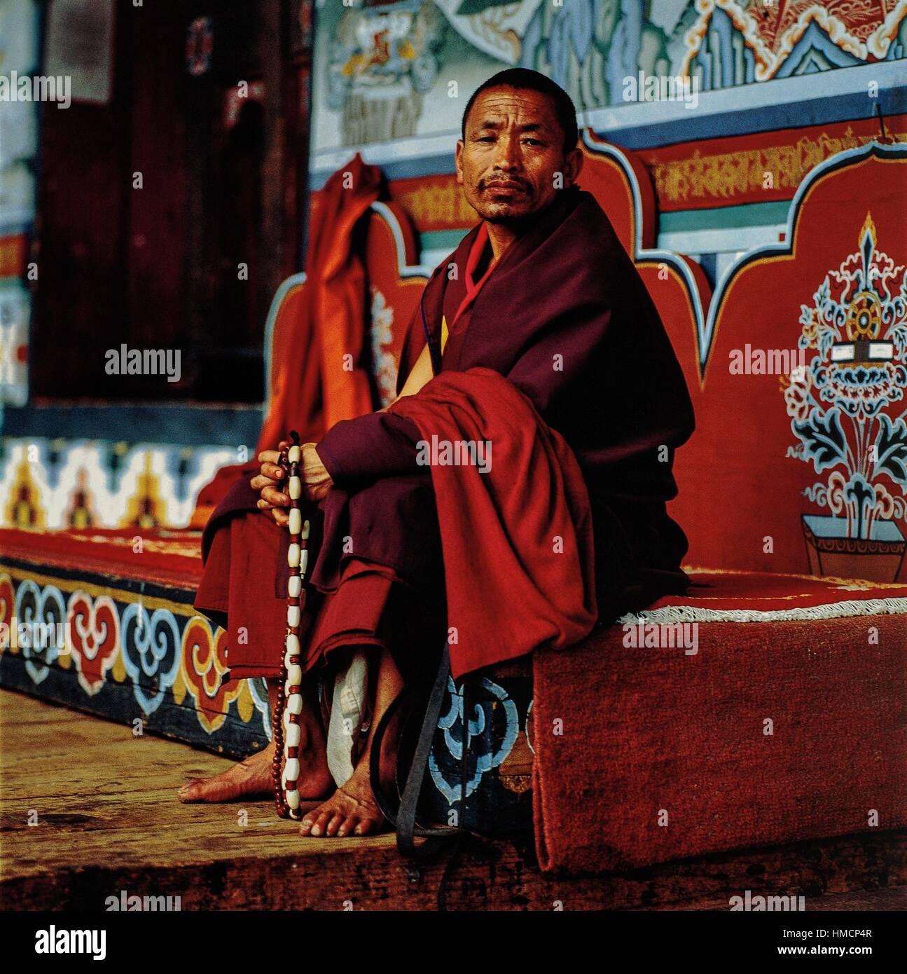 Lama praying in the Taktsang Palphug monastery, also known as Paro Taktsang or Tiger's nest, Bhutan. - Stock Image