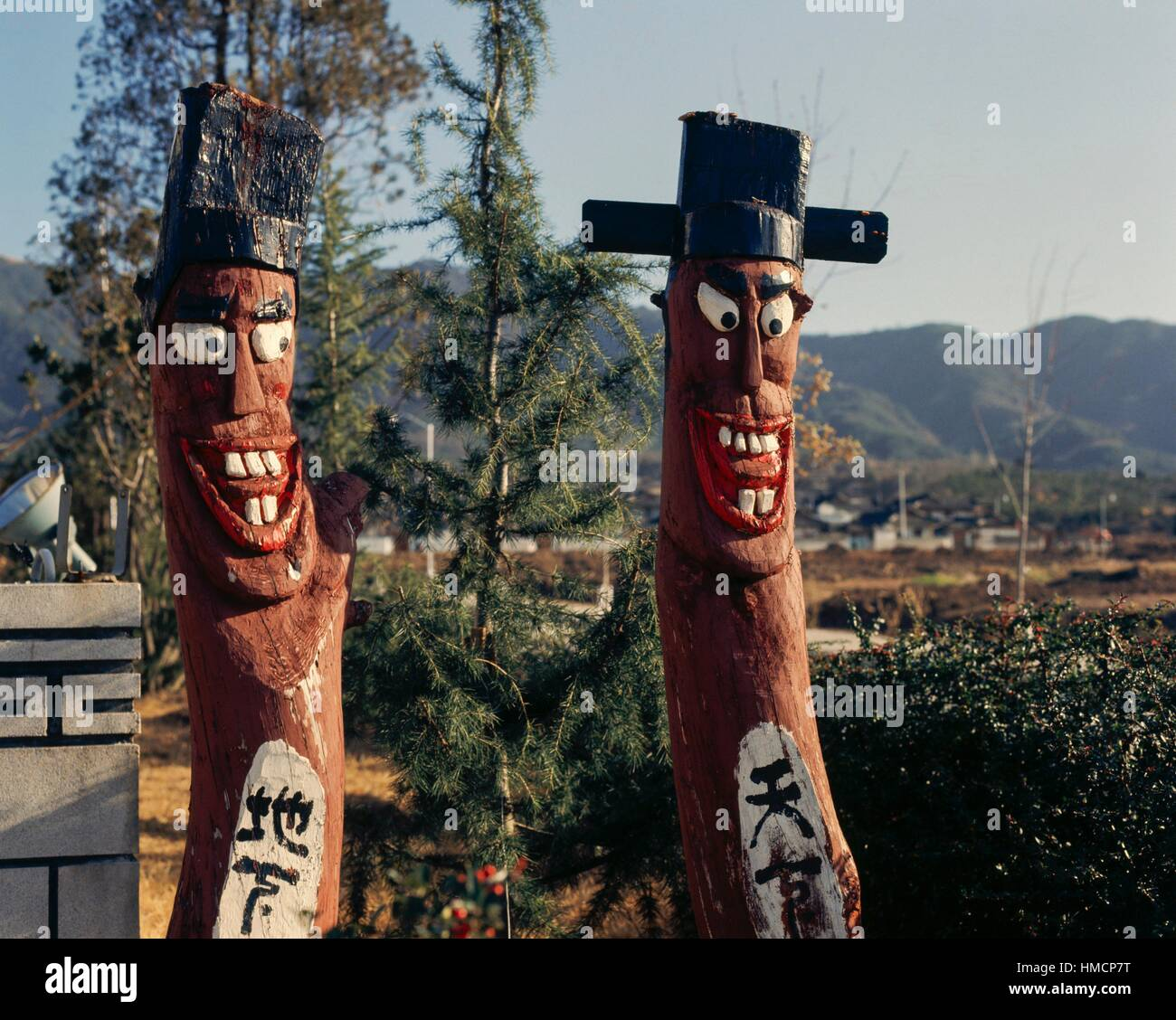 Carved wooden totems with painted faces, South Korea. - Stock Image