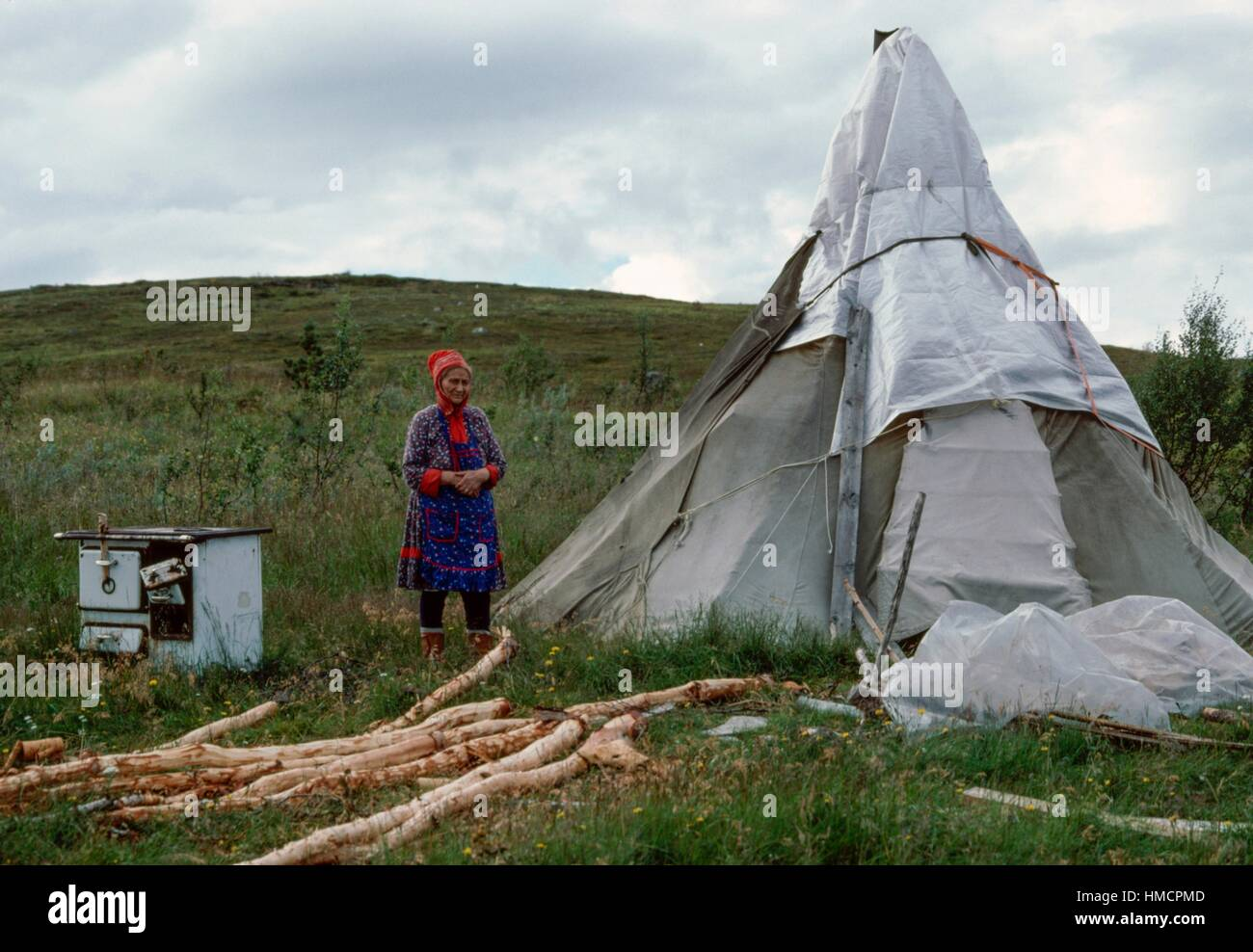 Sami (Laplander) woman next to a traditional tent, Norway. - Stock Image
