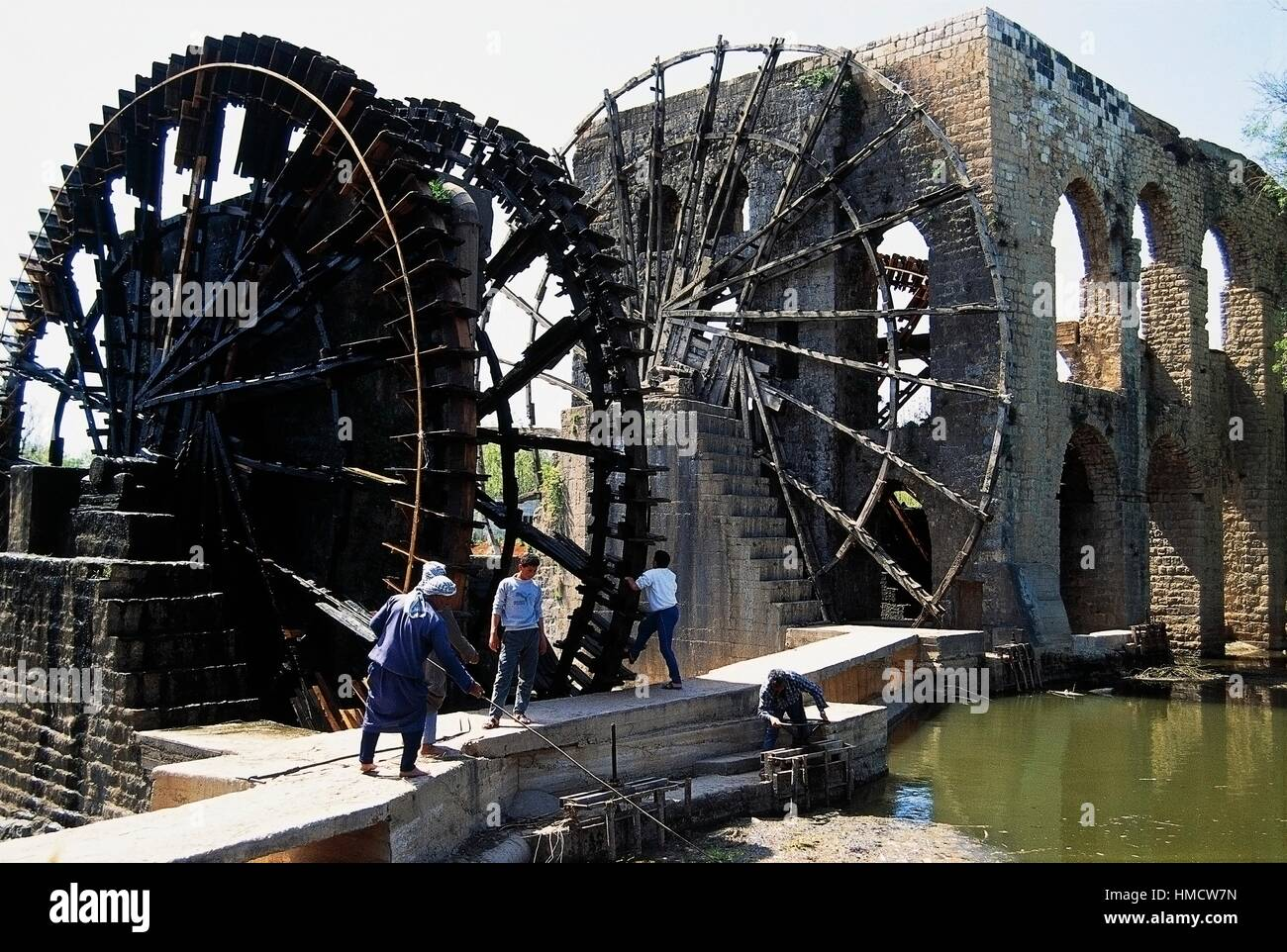 Men working in front of the noria, water wheels, on the Hama River, Haman, Syria. - Stock Image