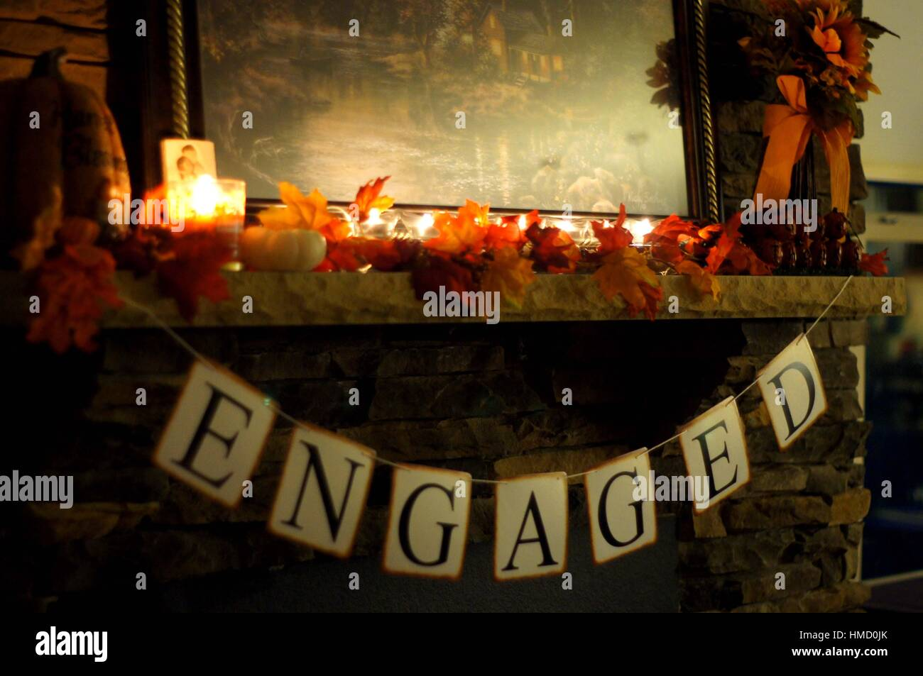 Engagement banner on mantle with candle light - Stock Image