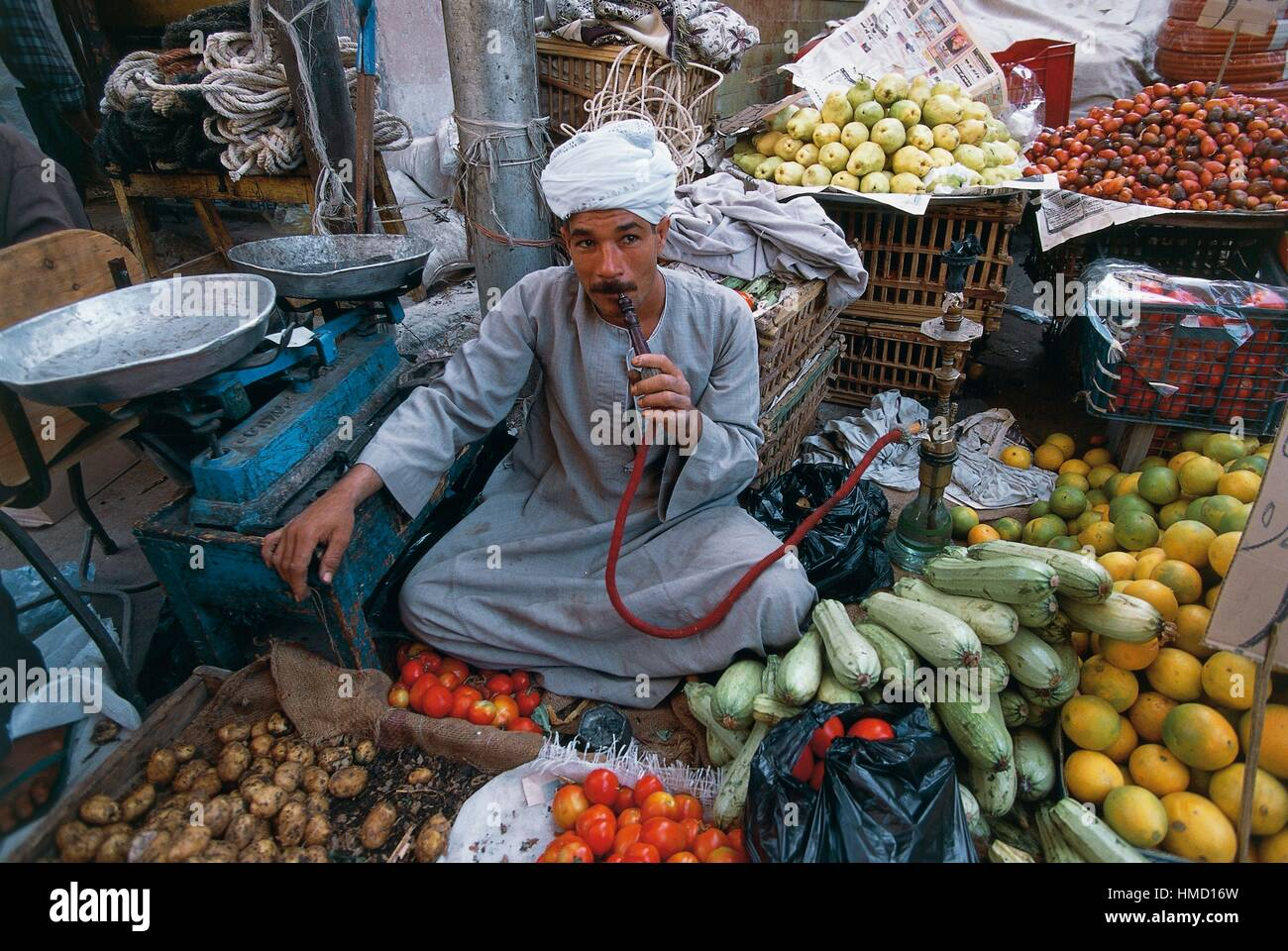 A fruit and vegetable vendor smoking a hookah, market in Luxor, Qena, Egypt. Stock Photo