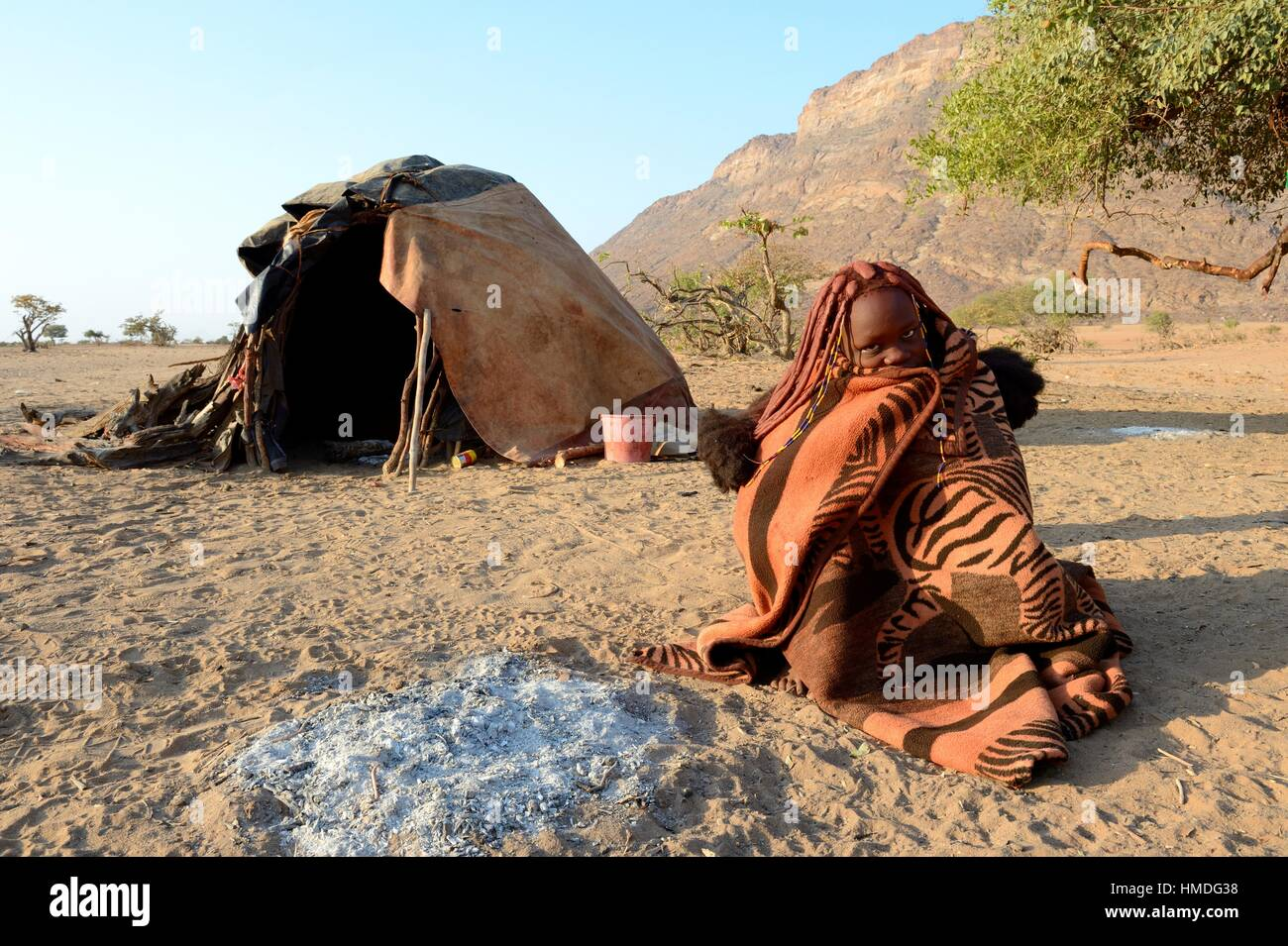 Himba woman early morning wrapped up in a blanket next to her open fireplace with her mud hut in the background. - Stock Image