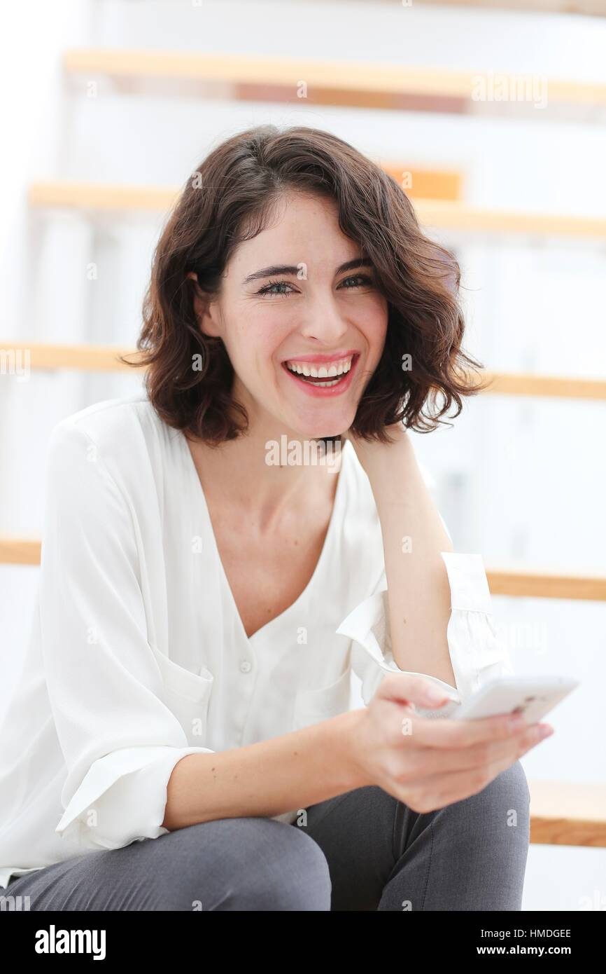Woman sitting on stairs and using smart phone - Stock Image