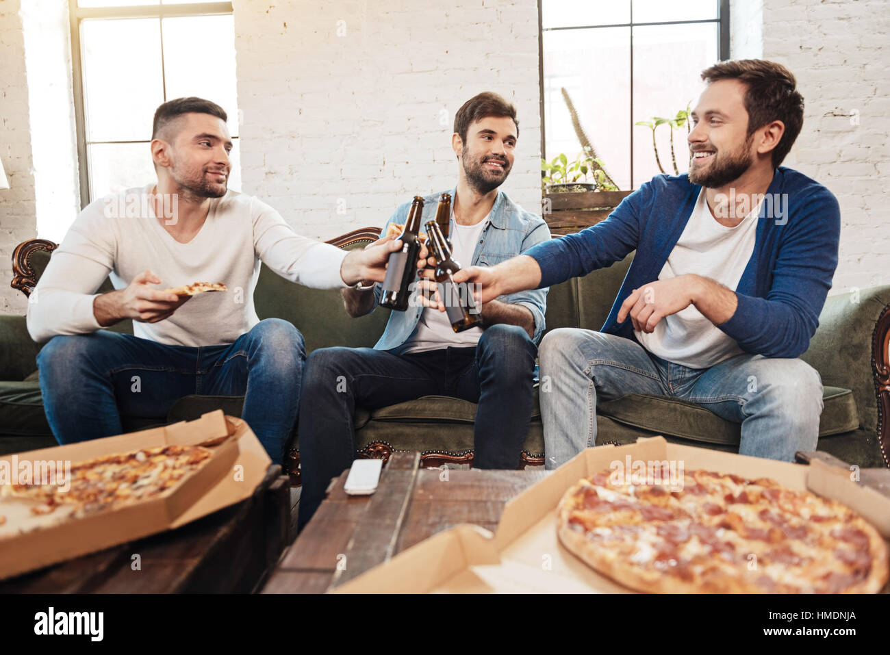 Delighted pleasant men drinking beer - Stock Image