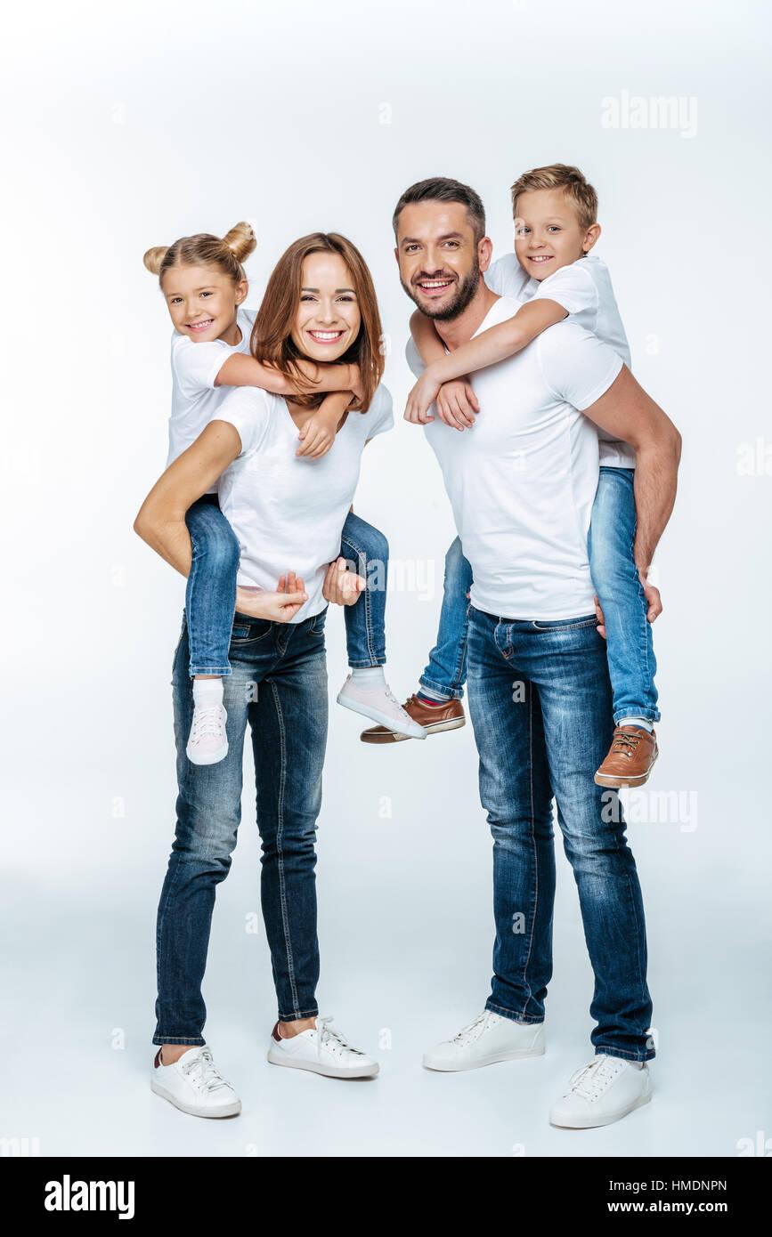 Parents piggybacking happy children - Stock Image
