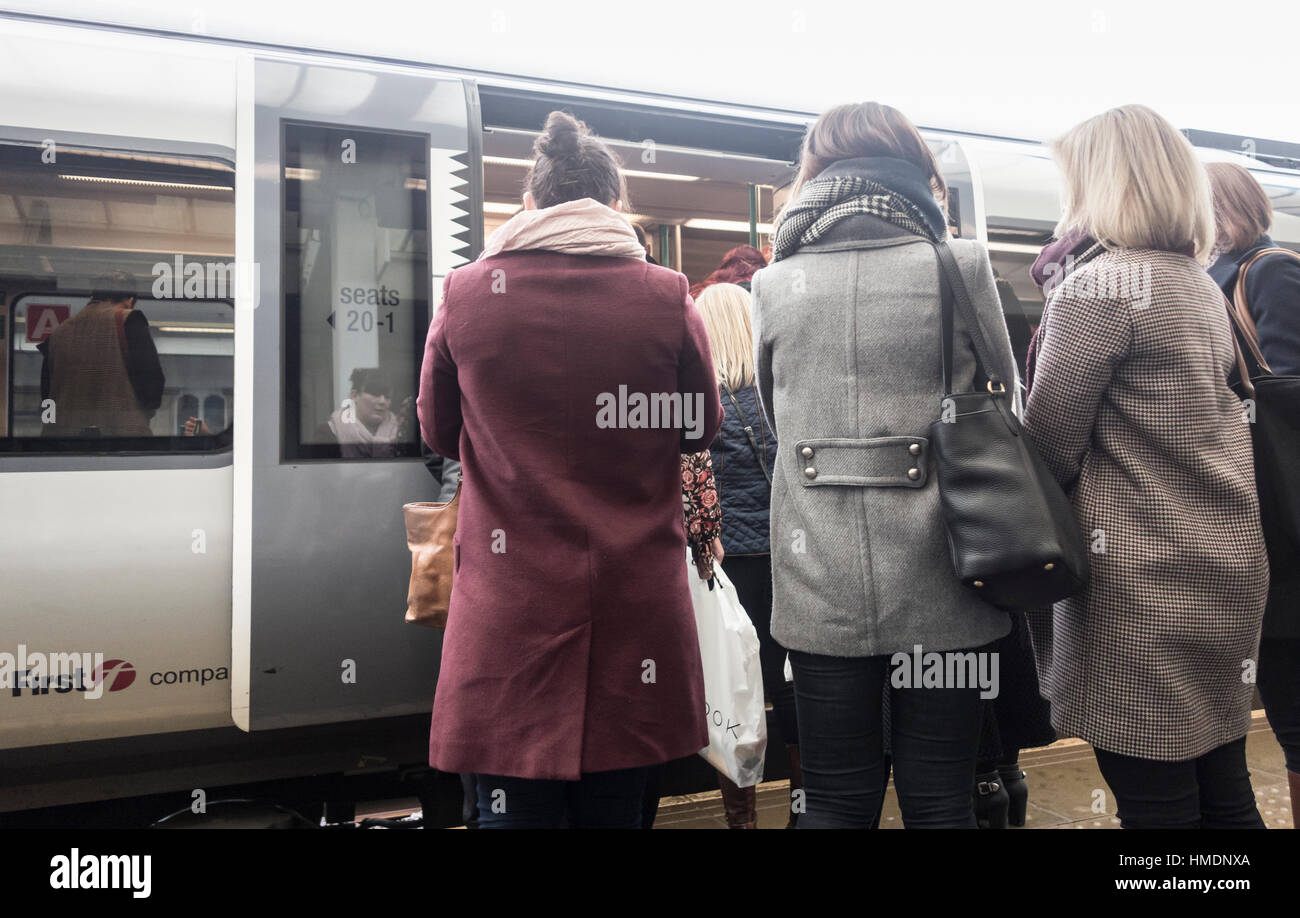People boarding train at UK Railway station - Stock Image