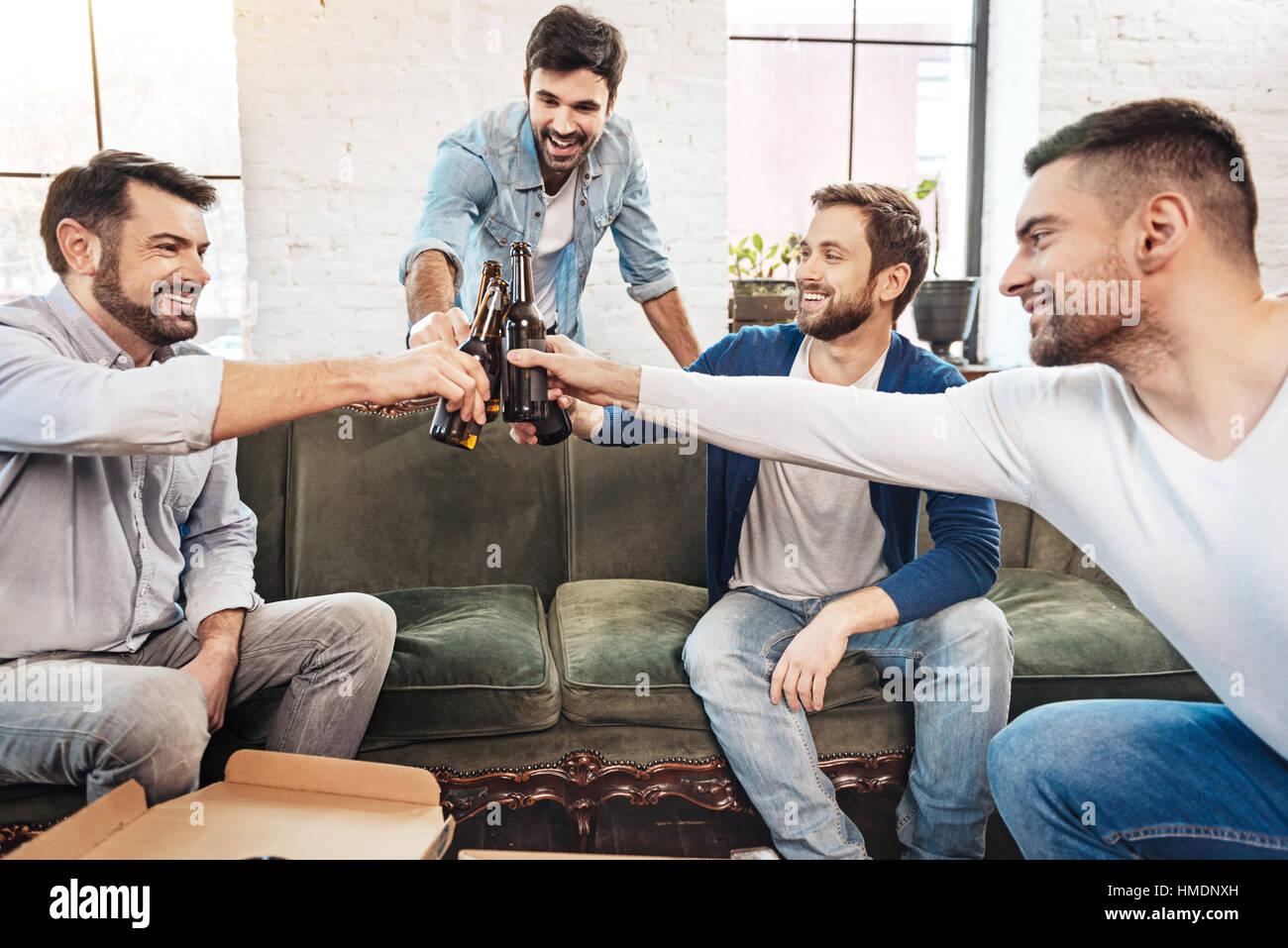 Joyful positive men clinking bottles - Stock Image
