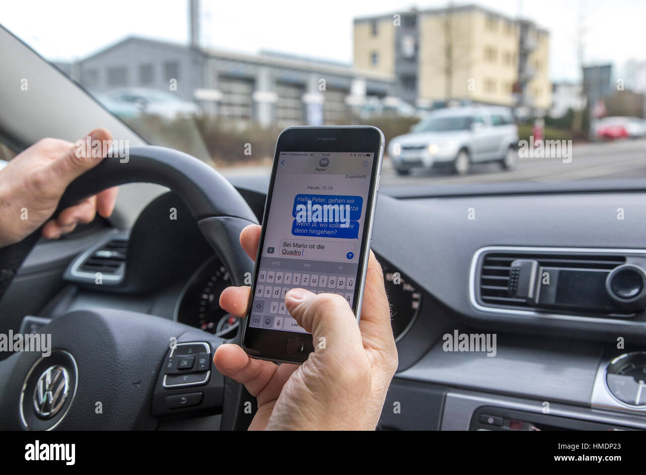 A car driver is using a mobile phone, smartphone, while driving the car, reading SMS messages, - Stock Image